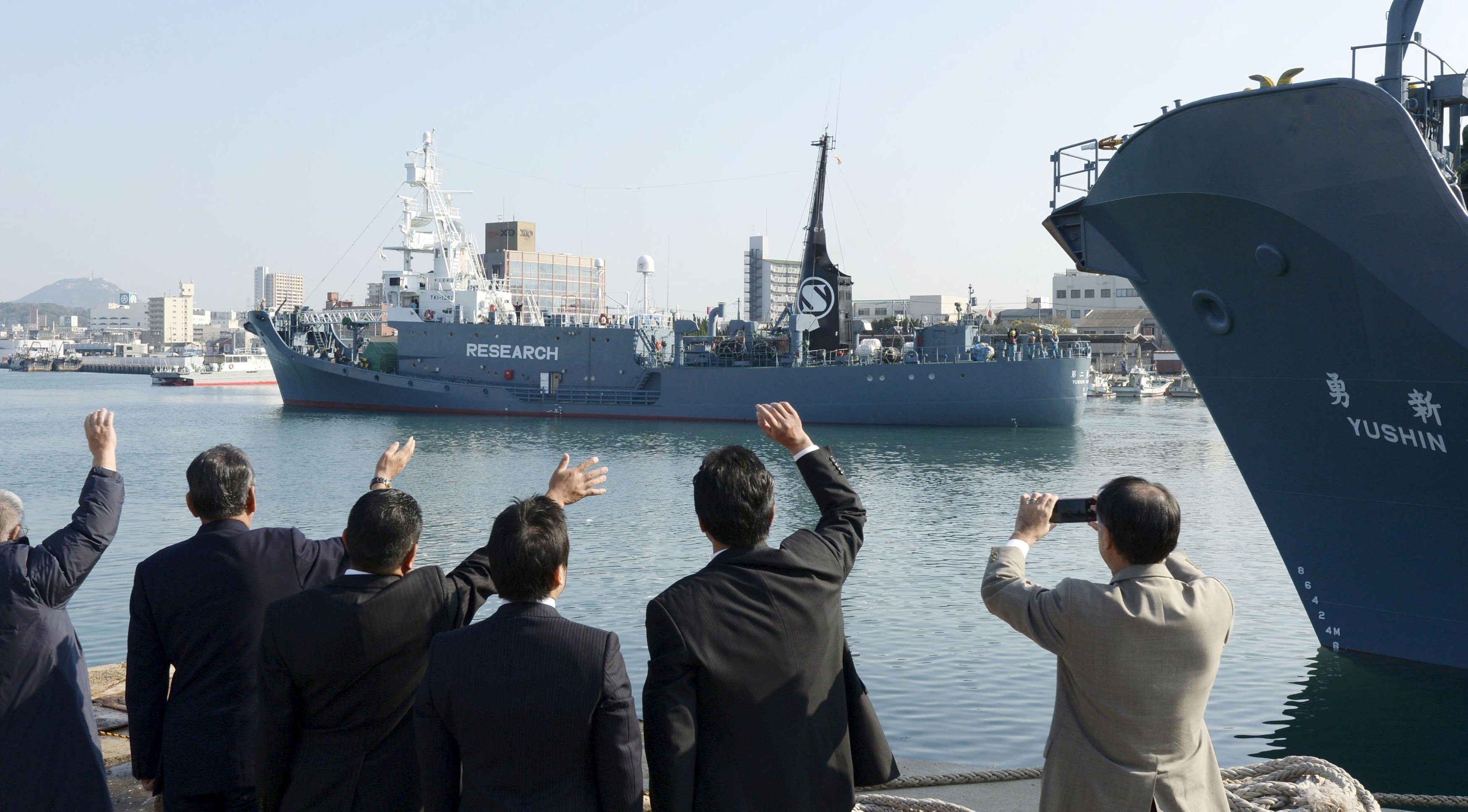 Officials wave as Japanese whaling vessel Yushin Maru No.2 leaves for the Antartic Ocean at a port in Shimonoseki, southwestern Japan on Dec. 1, 2015.