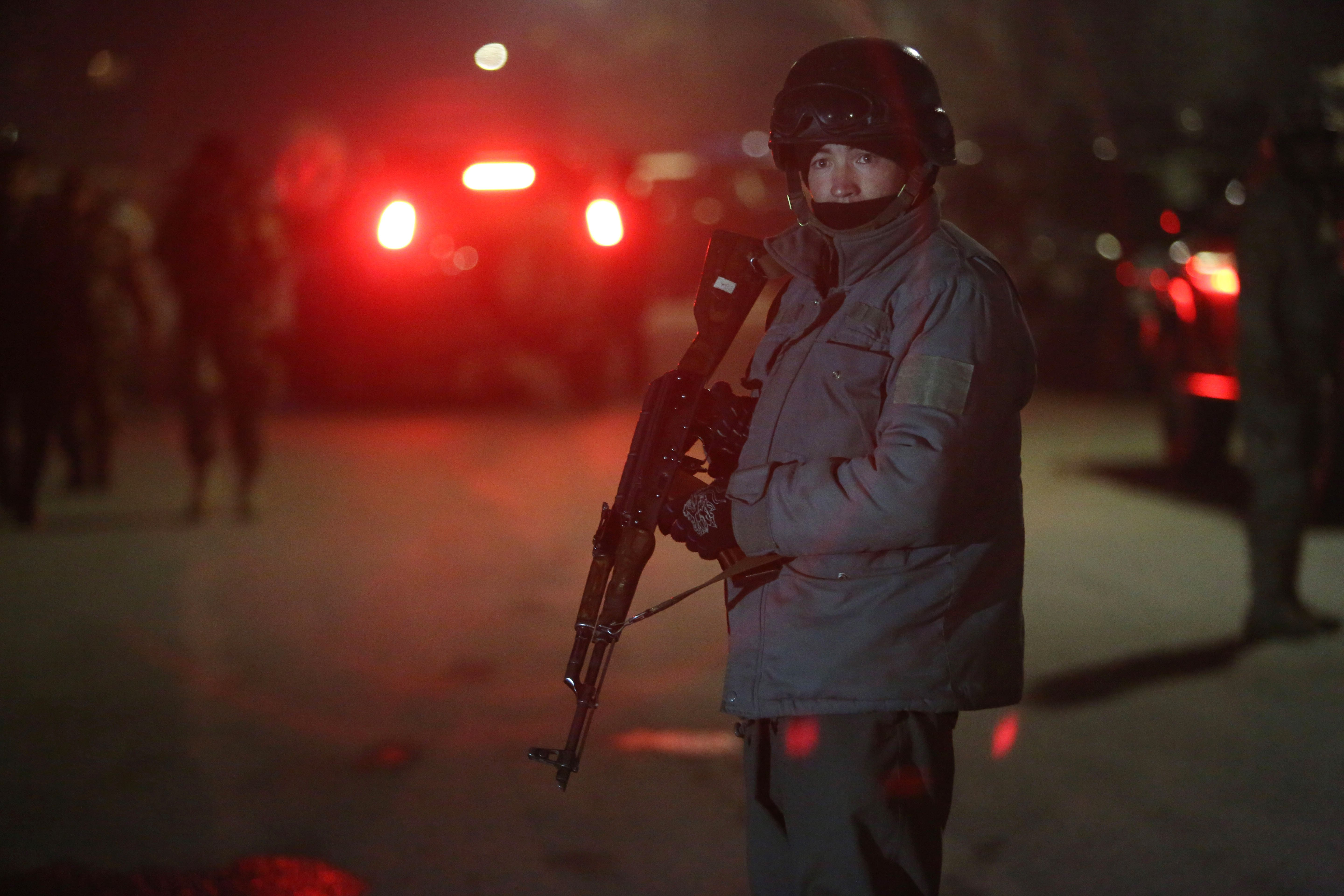 A member of Afghan security forces stands guard at the site of a car bomb attack by Taliban militants near a foreign guesthouse in Kabul, Dec. 11, 2015.