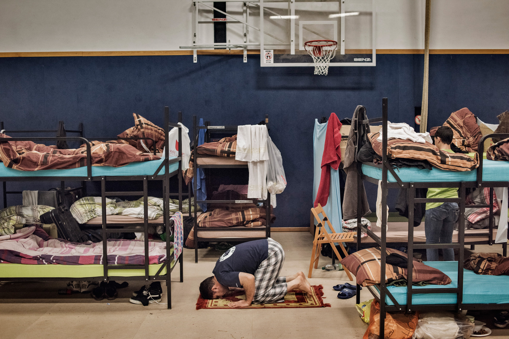 An asylum seeker prays on the floor of a shelter in Prenzlauer Berg, a locality in northeastern Berlin. Some 200 refugees were housed in less than two hours by German volunteers.From  Person of the Year.  December 21, 2015 issue.