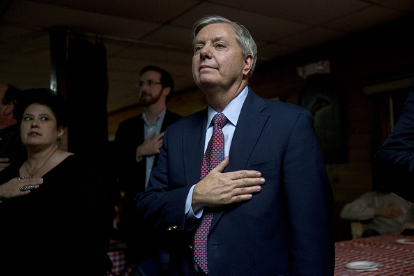Senator Lindsey Graham, a Republican from South Carolina and 2016 presidential candidate, right, places his hand over his heart during the Pledge of Allegiance at the Stafford County GOP Christmas Party during a campaign stop at Newick's Lobster House in Dover, New Hampshire, U.S., on Friday, Dec. 18, 2015.