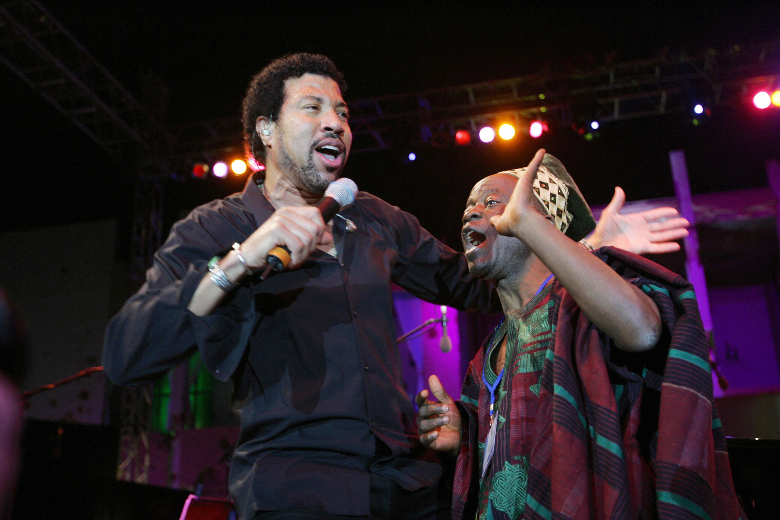 Lionel Richie performs with an unidentified man during a concert held in front of the house of Libyan leader Muammar Gadhafi in Tripoli on April 14, 2006.