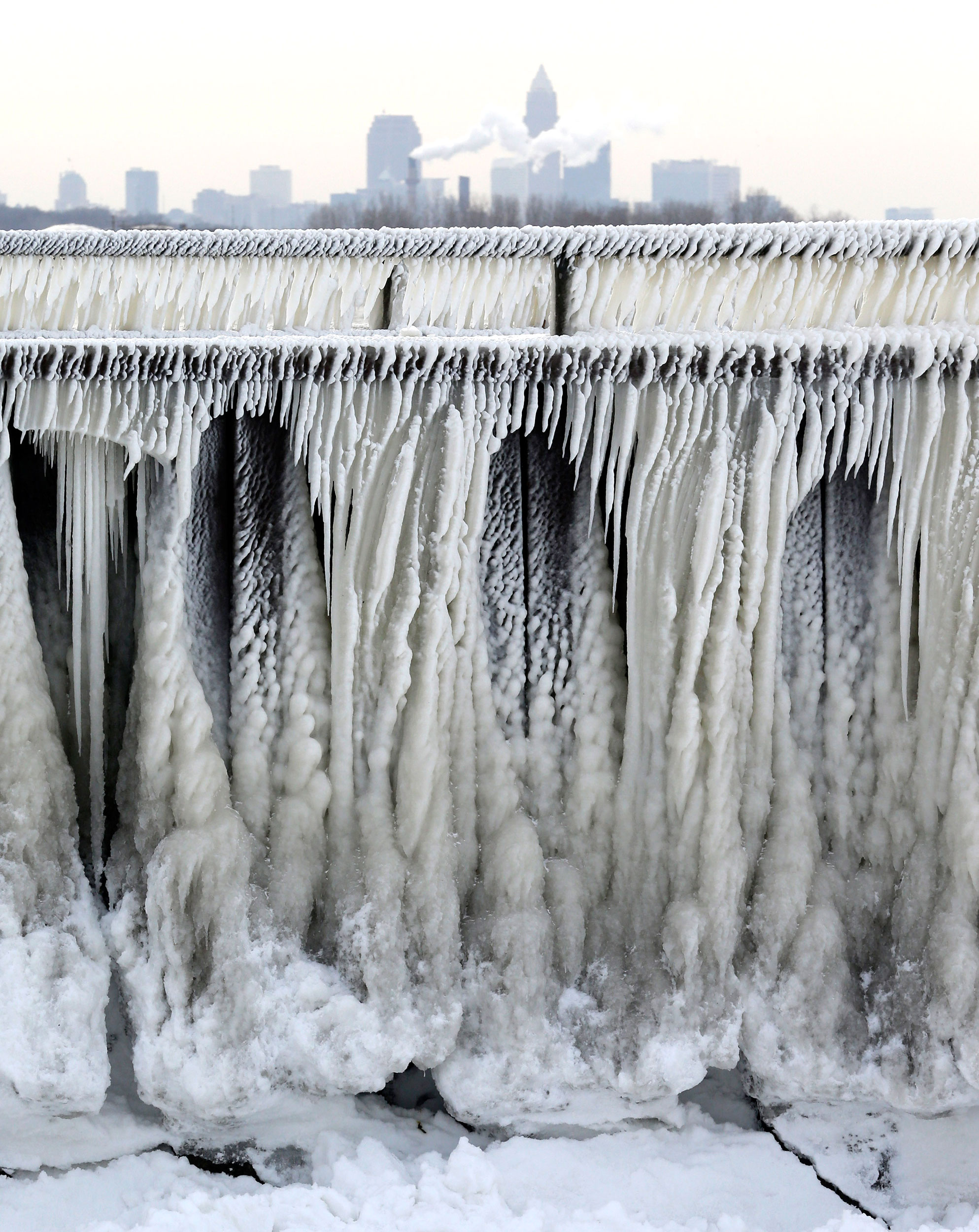 Ice from Lake Erie forms on a pedestrian walkway with a view of Cleveland, Ohio in the background on Jan. 8, 2015.