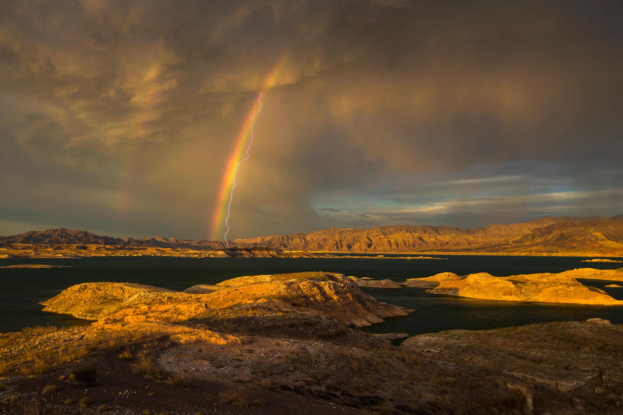 Lightning strikes near a rainbow over Lake Mead National Recreation Area Lake Mead, Nevada on July 1, 2015.