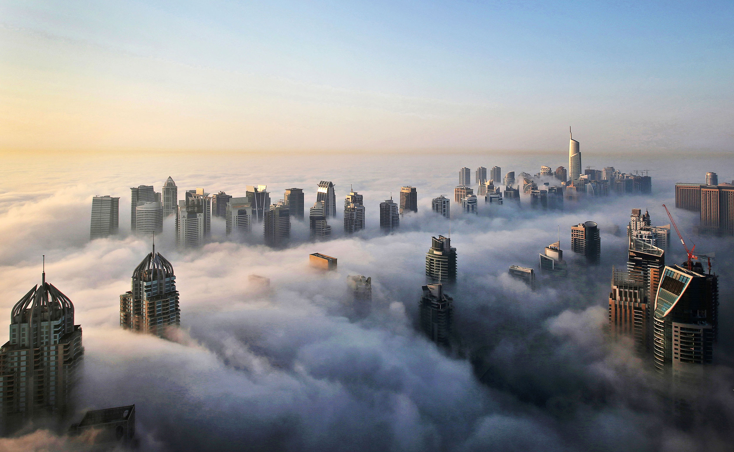 A thick blanket of early morning fog partially shrouds the skyscrapers of the Marina and Jumeirah Lake Towers districts of Dubai on Oct. 5, 2015.