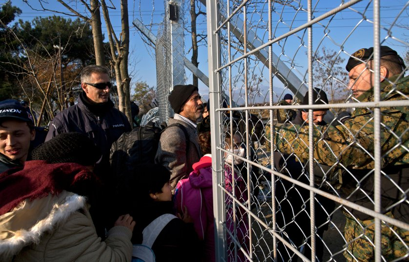Qasu and his family approach Macedonian army officers as they cross a fence at the Greek-Macedonian border, near the northern Greek village of Idomeni, Dec. 5, 2015. The Qasus traveled via midnight ferry to Athens and then by bus to Greece's northern border.
