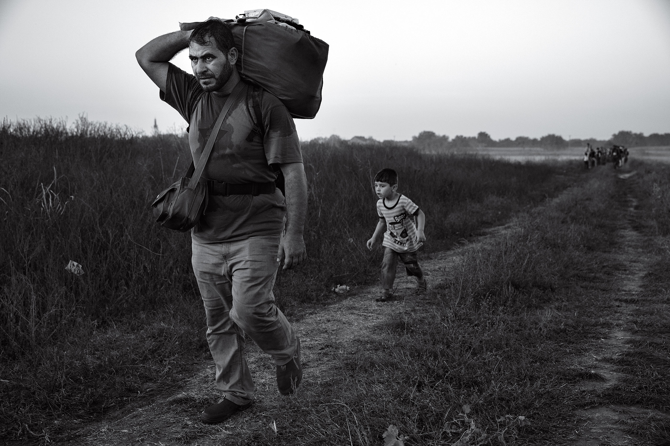 A man walks with his son behind him as they make their way to the train station in Tovarnik, Croatia, on the border with Serbia. In the Balkans, many migrants began traveling by foot, echoing more ancient journeys, Sept. 17, 2015.From  James Nachtwey: The Journey of Hope