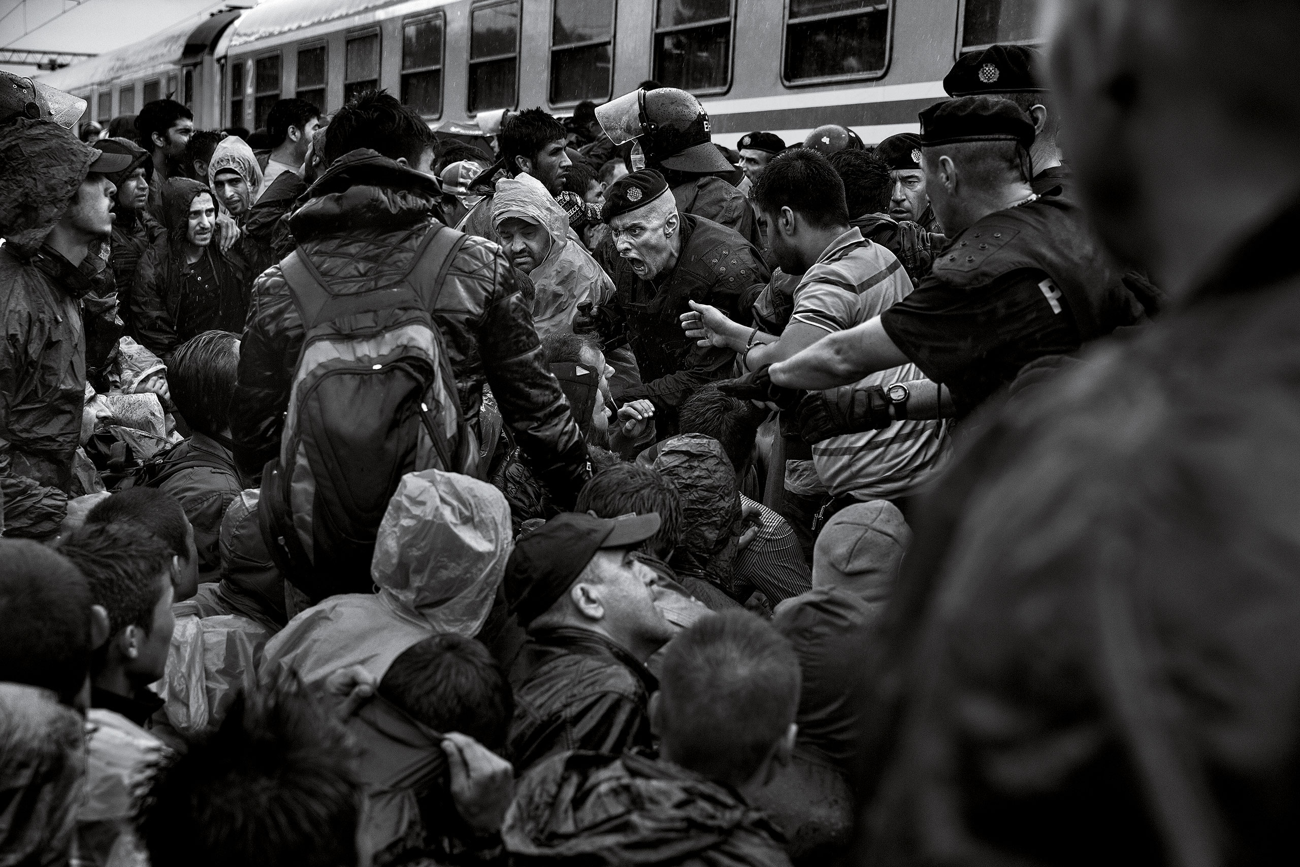 A police officer screams at refugees as they attempt to board a train in Tovarnik, Croatia, Sept. 17, 2015.From  James Nachtwey: The Journey of Hope