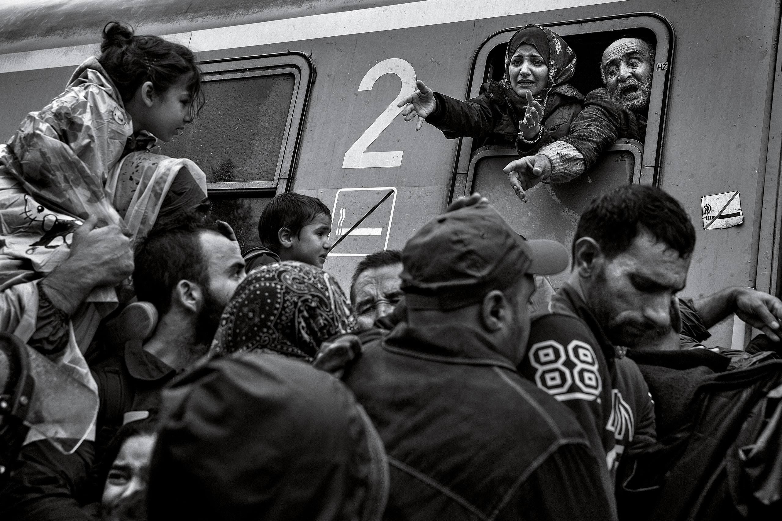 Refugees plead with police officers to let members of their families board the train in Tovarnik, Croatia, Sept. 17, 2015.From  James Nachtwey: The Journey of Hope