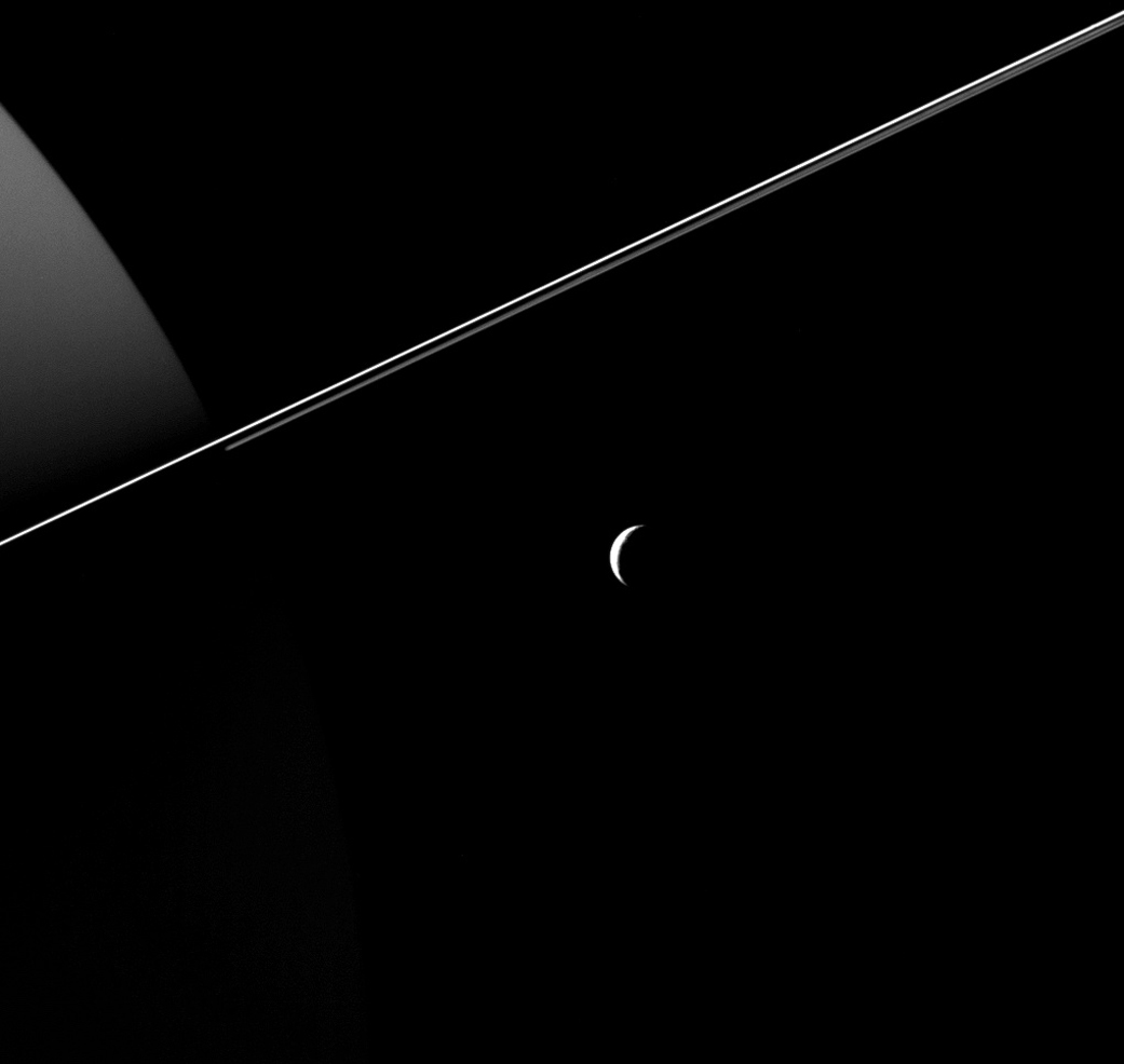 Saturn is all about geometry—an ever-changing juxtaposition of finely etched shapes. Here the 657-mile moon Tethys is seen in its crescent phase in the foreground, with the razor edge of Saturn's rings slicing through the frame and the bulk of Saturn itself in the background.