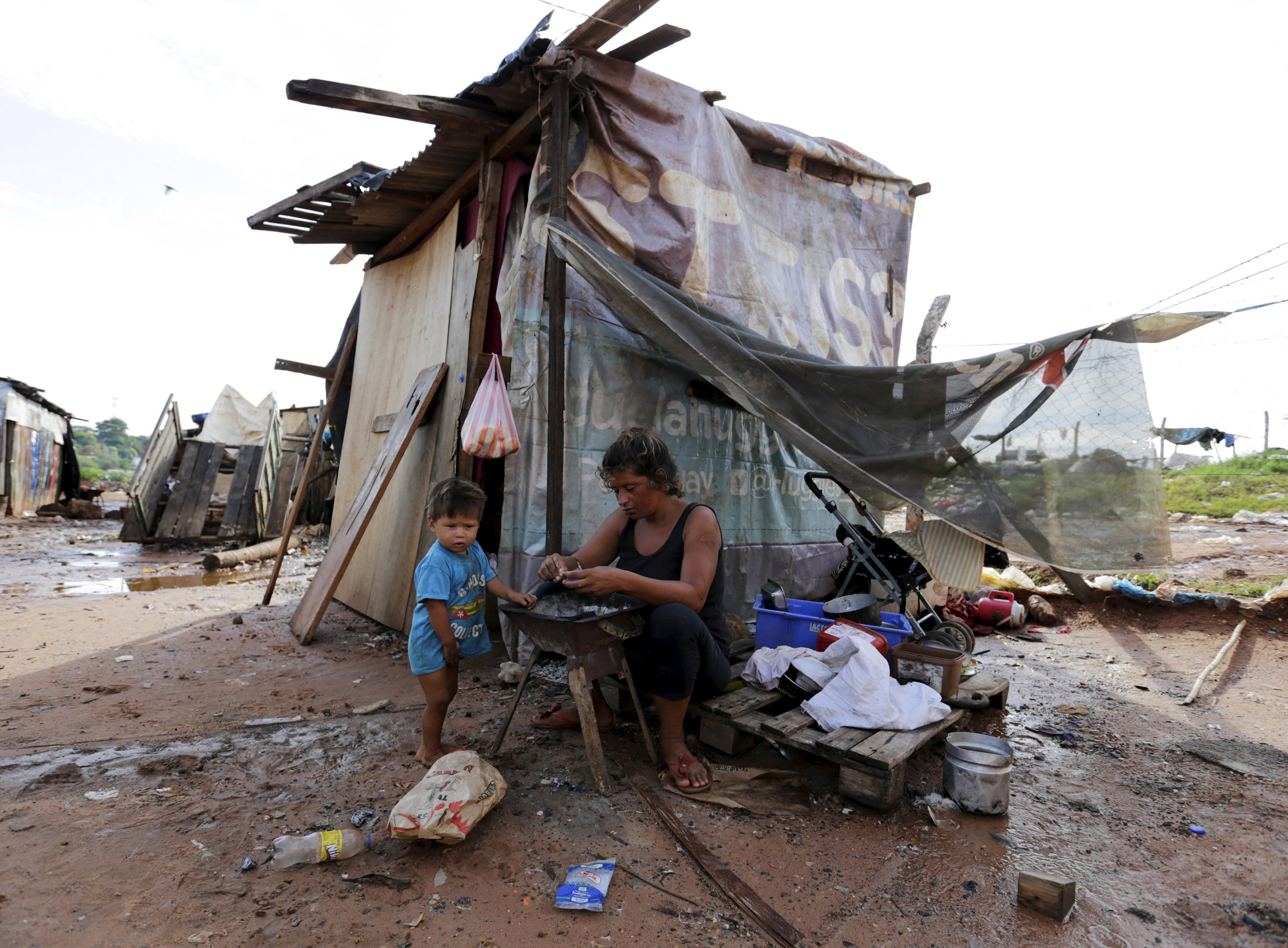 A woman sits next to a makeshift shelter with her son in Asuncion on Dec. 27, 2015.