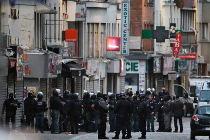 Police officers gather in the northern Paris suburb of Saint-Denis as special forces raid an apartment on Nov. 18, 2015.