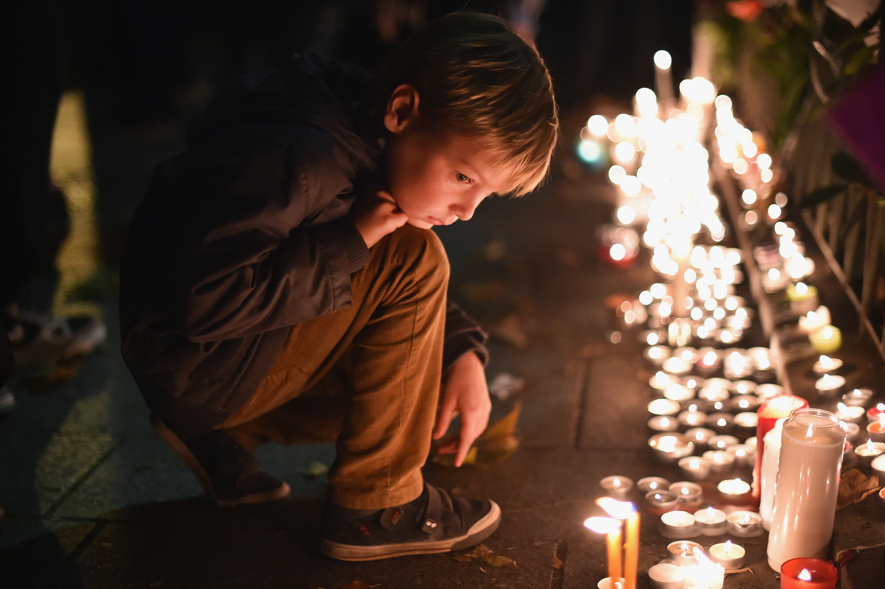 A young boy views tributes following terrorist attacks in Paris, on Nov. 16, 2015.