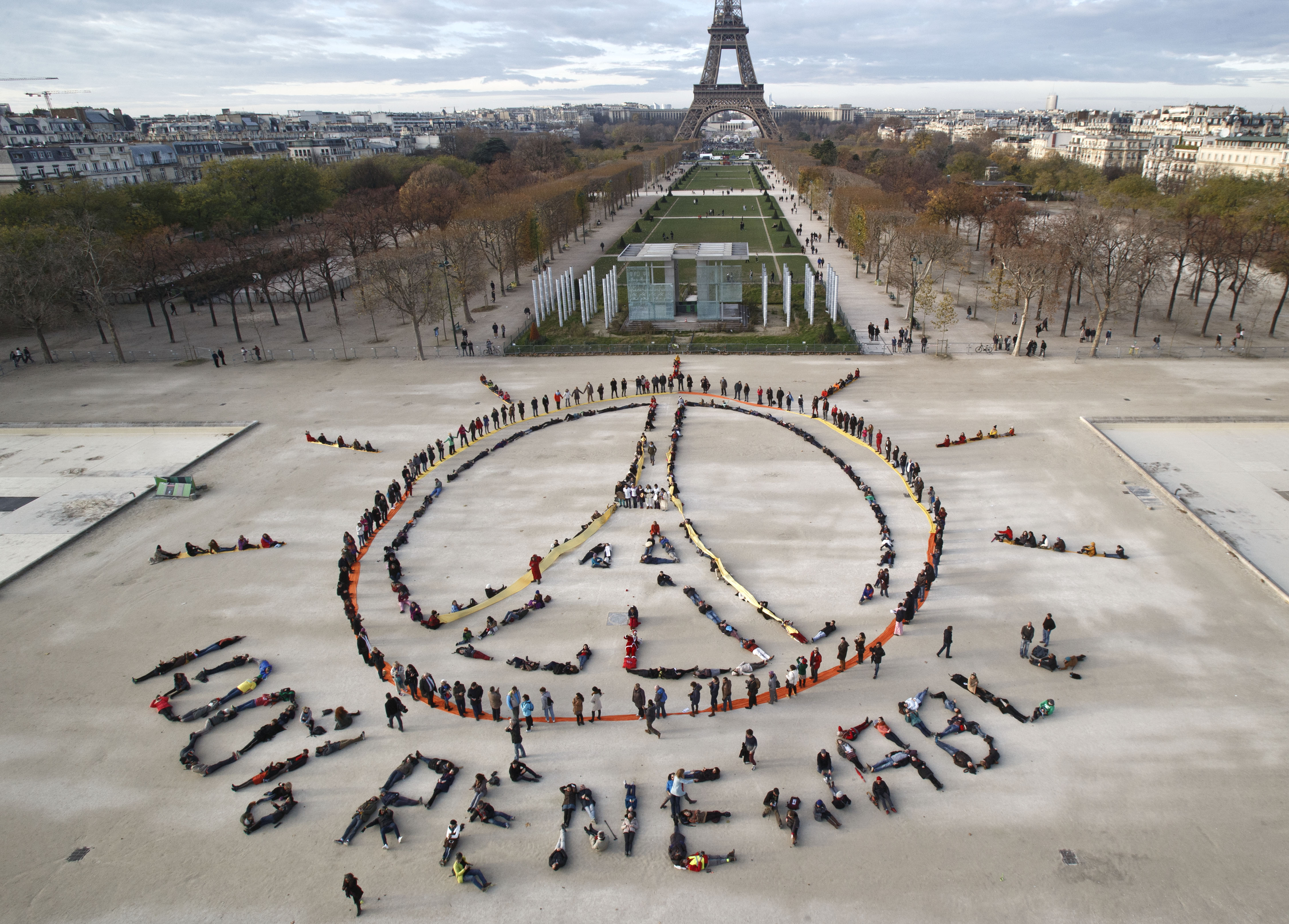 Environmentalist activists form a human chain representing the peace sign and the spelling out  100% renewable , on the side line of the COP21, United Nations Climate Change Conference near the Eiffel Tower in Paris on Dec. 6, 2015.