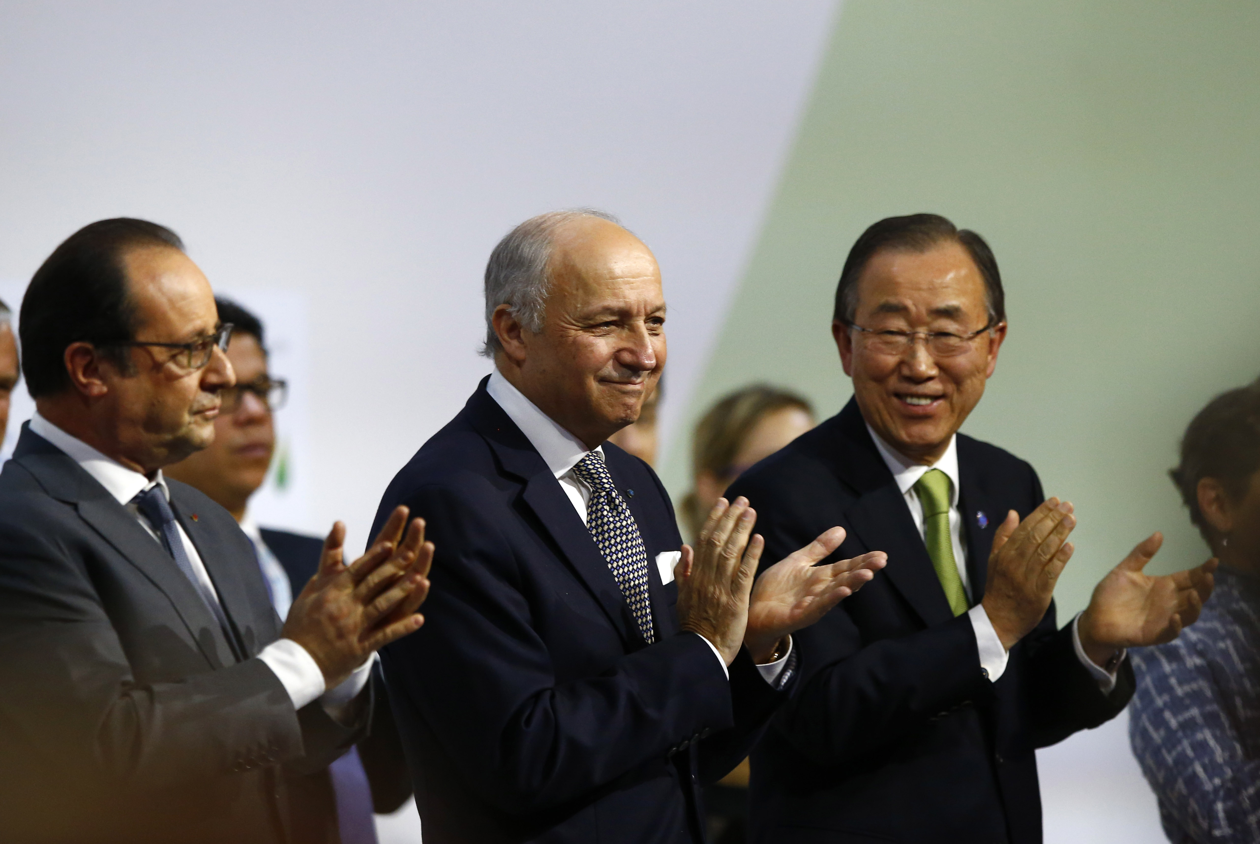 Francois Hollande, Laurent Fabius and Ban Ki-moon applaud at the COP21, the United Nations Climate Change Conference, in Le Bourget, north of Paris, on Dec.12, 2015.
