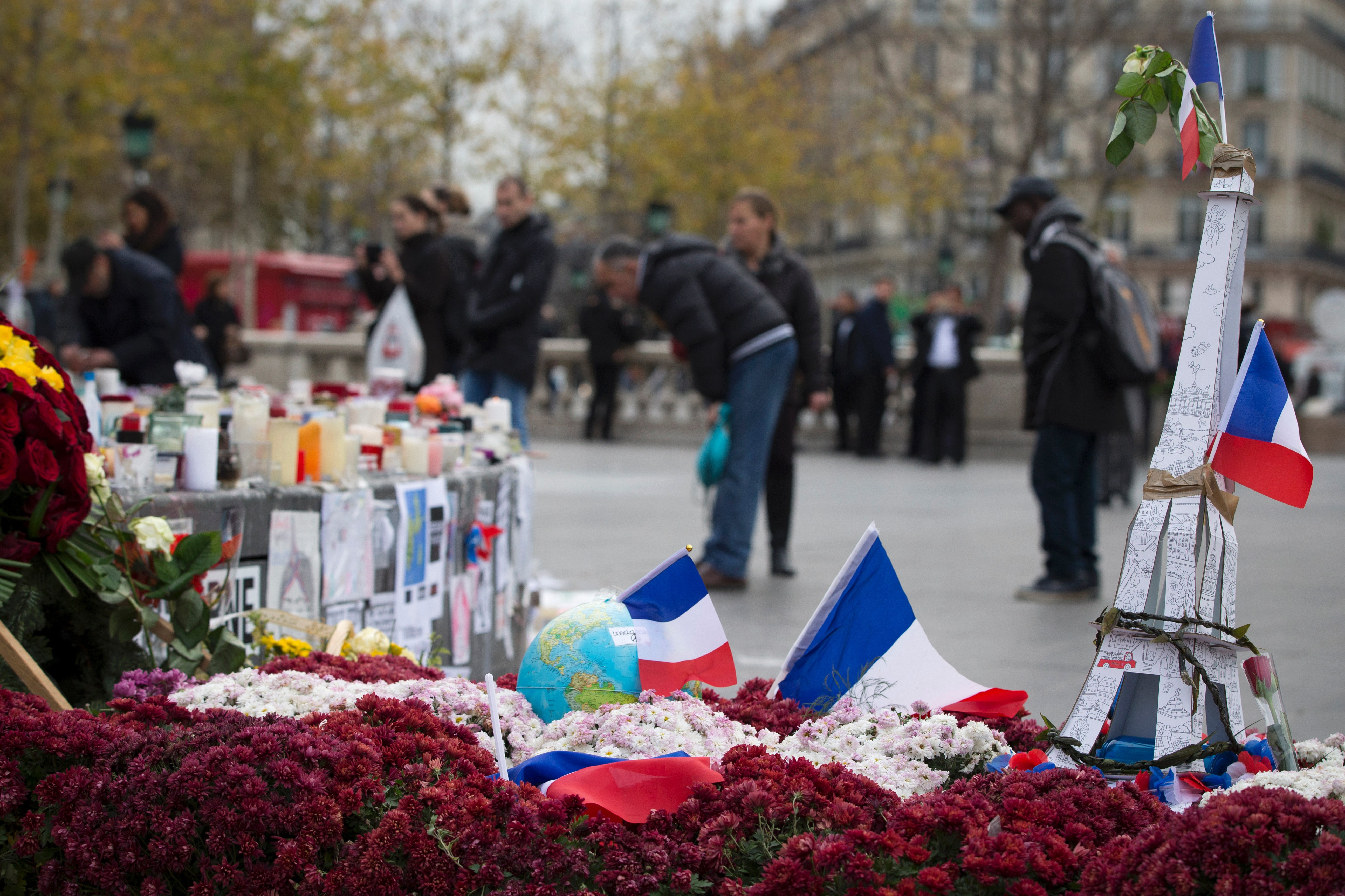 People stand on the Place de la Republique in Paris on December 2, 2015, next to a model Eiffel Tower, flowers and French flags layed in memory of the victims of the deadly attacks in and around Paris on Nov. 13.