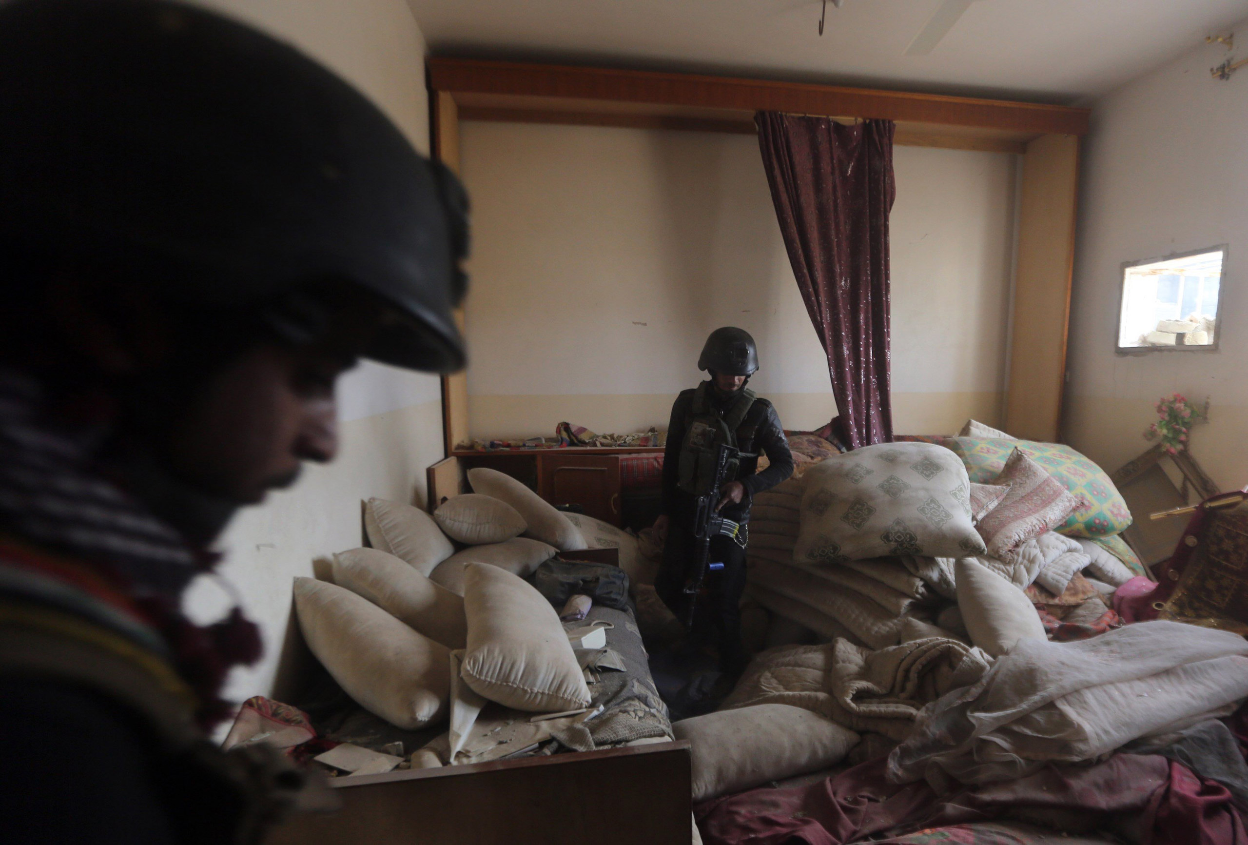 Members of Iraq's elite counter-terrorism units search a building during military operations after ISIS fighters abandoned their stronghold in Ramadi on Dec. 27, 2015.