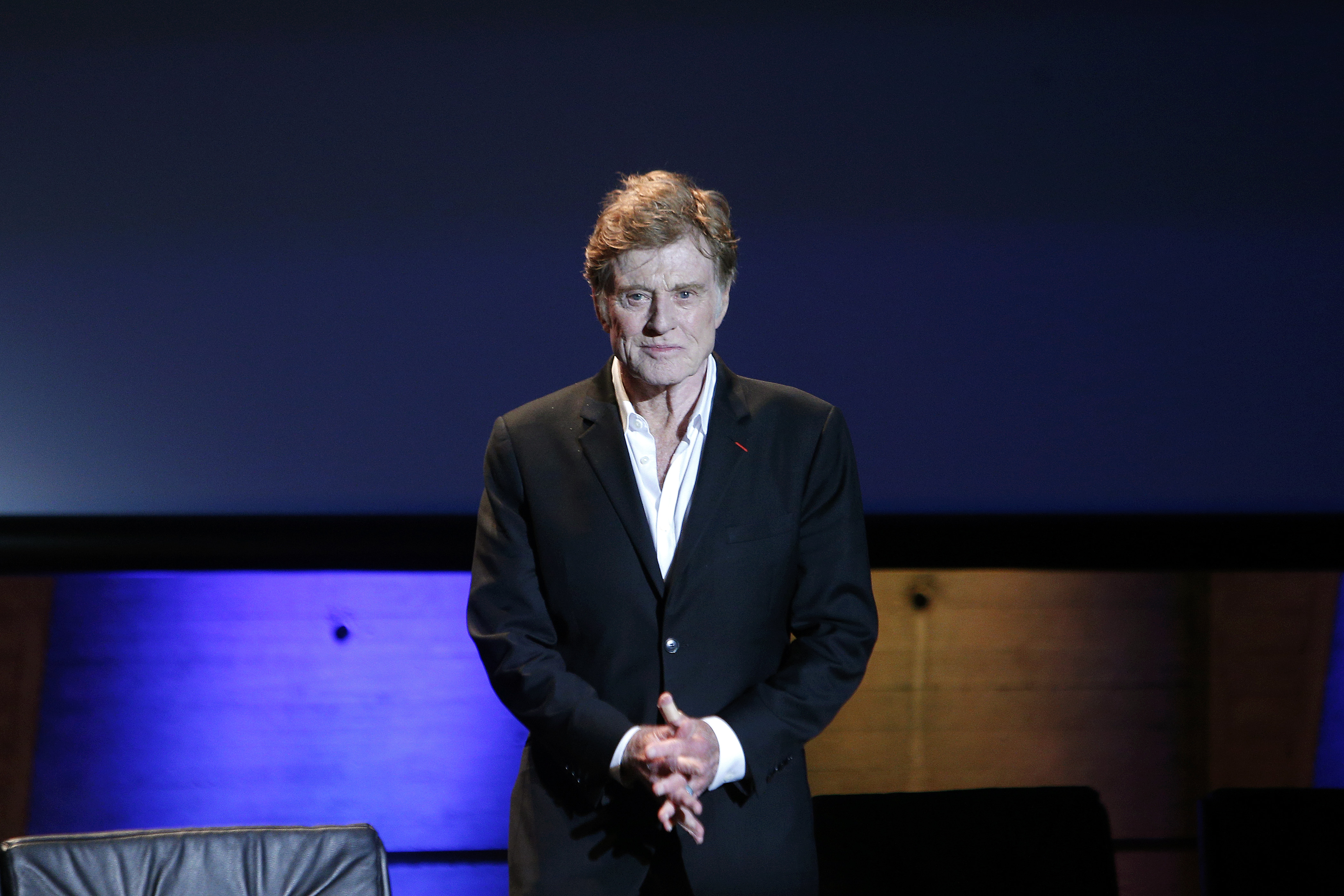 Robert Redford arrives on stage during a conference on climate at the UNESCO headquarters in Paris on Dec. 6, 2015.