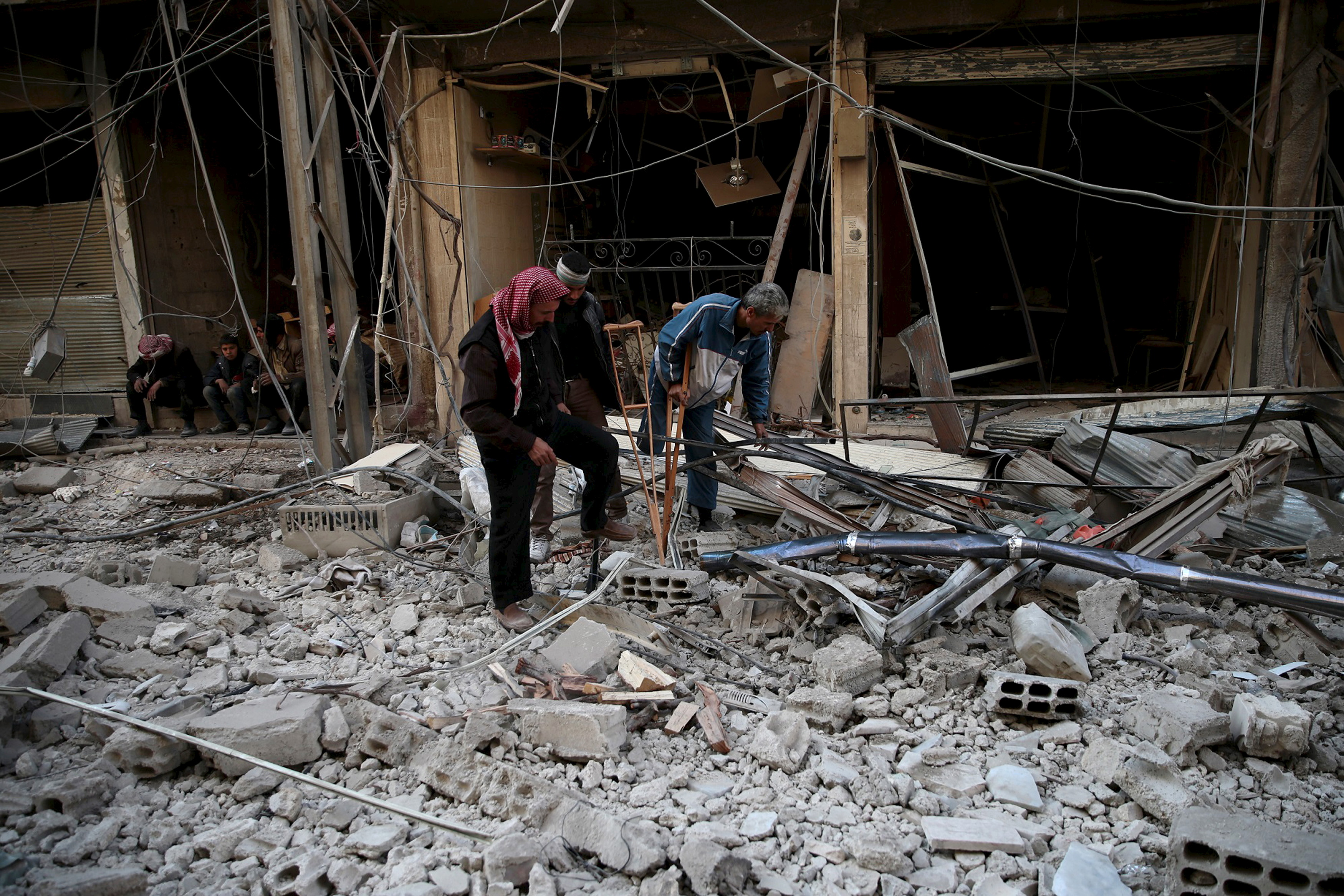 Men search for belongings at a site hit by missiles in the Douma neighborhood of Damascus on Dec. 13, 2015