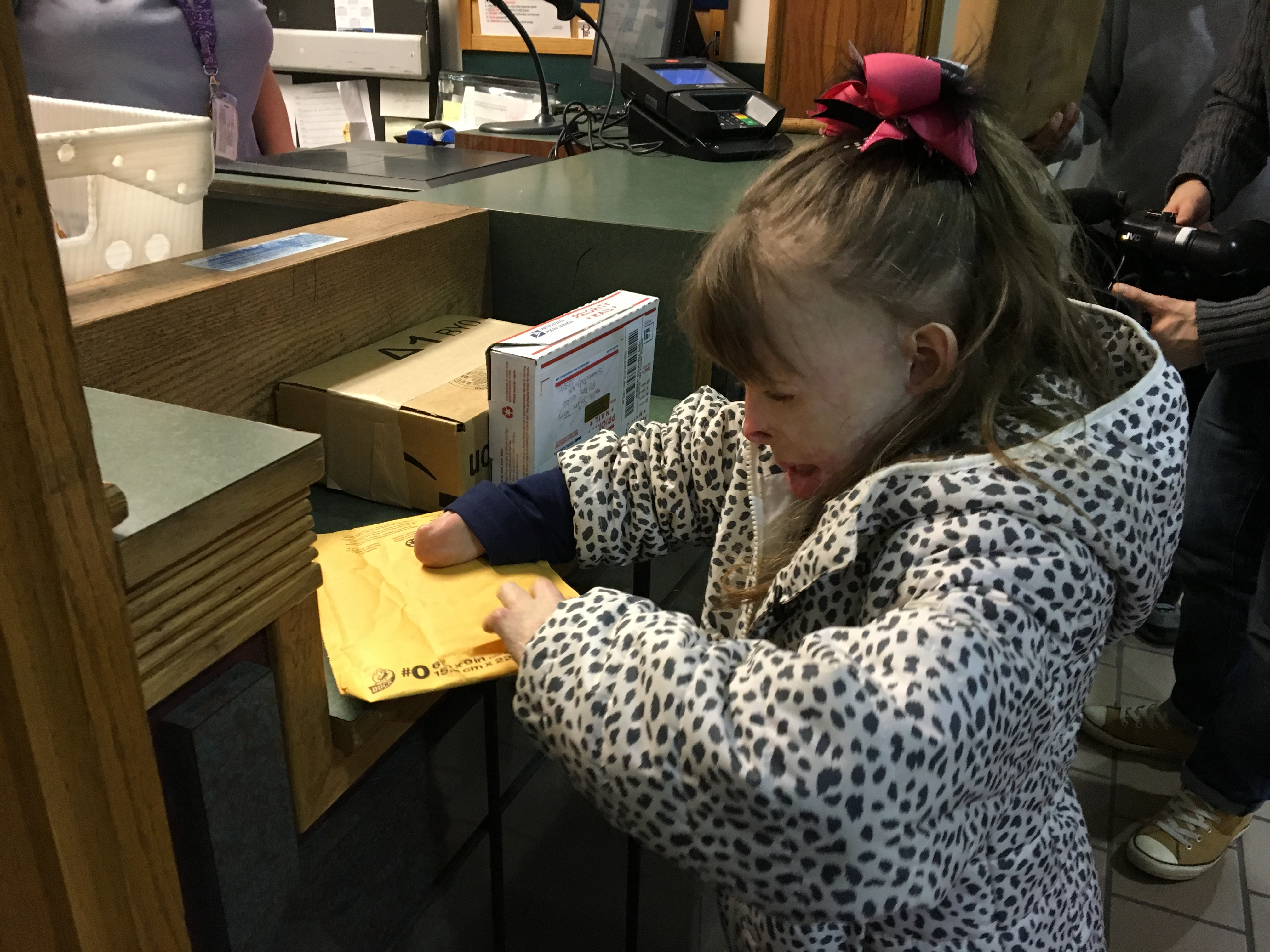 Safyre Terry opens a gift at a post office near her home in Rotterdam, NY.