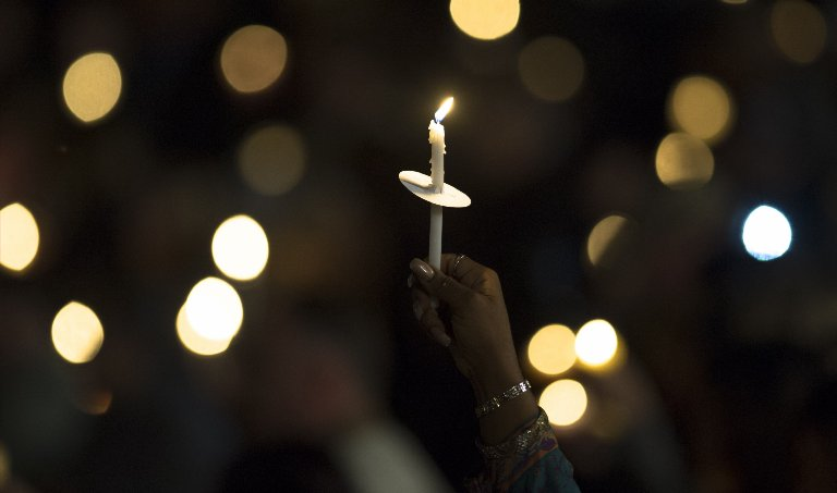 A mourner holds a candle as attending a vigil to pray for the victims of a mass shooting in San Bernardino, Calif. on Dec. 3, 2015.