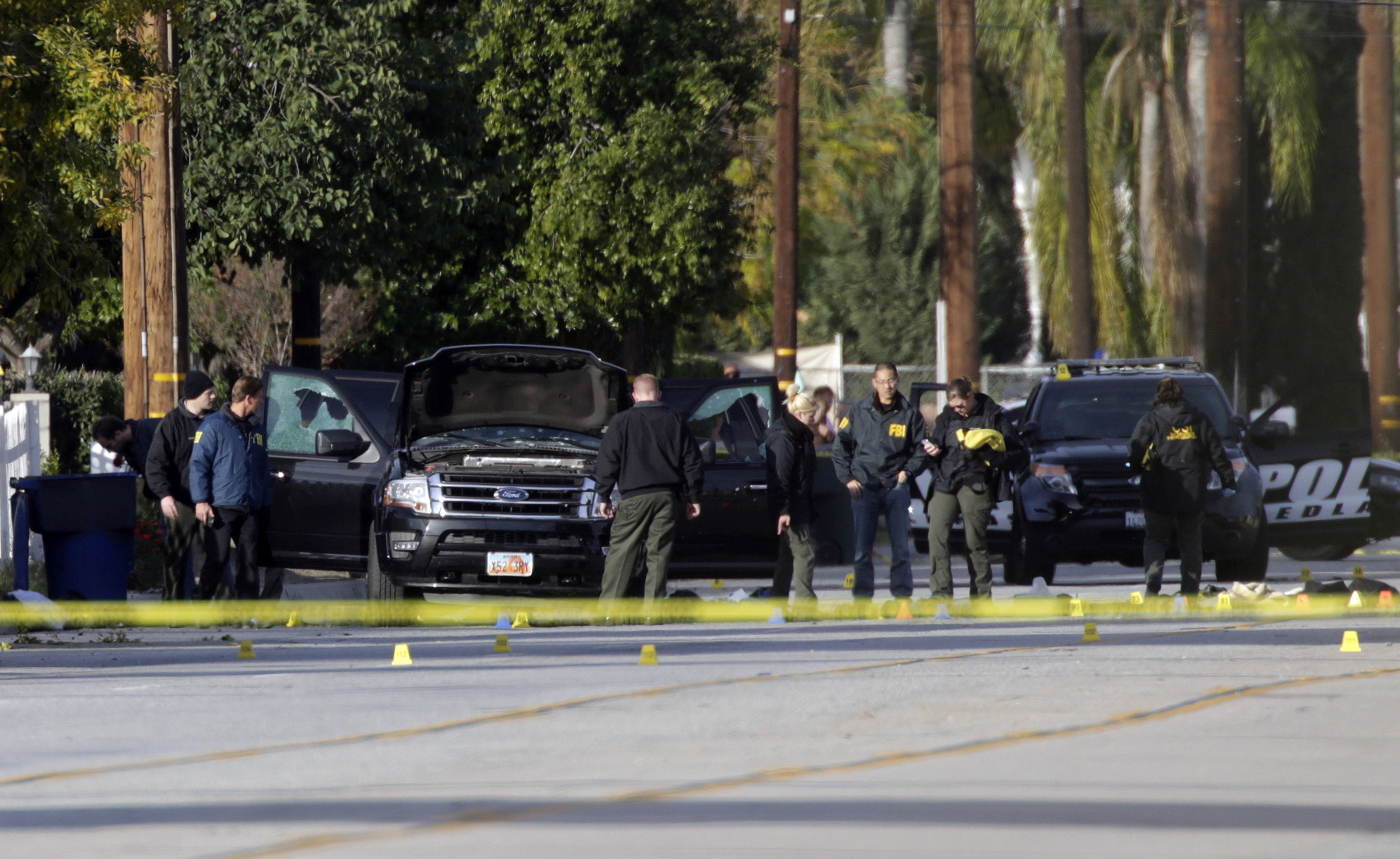 Law enforcement personnel continue to investigate on San Bernardino Avenue, where two suspects in the mass shooting at the Inland Regional Center died in a shootout with police in San Bernardino, Calif. on Dec. 3, 2015.