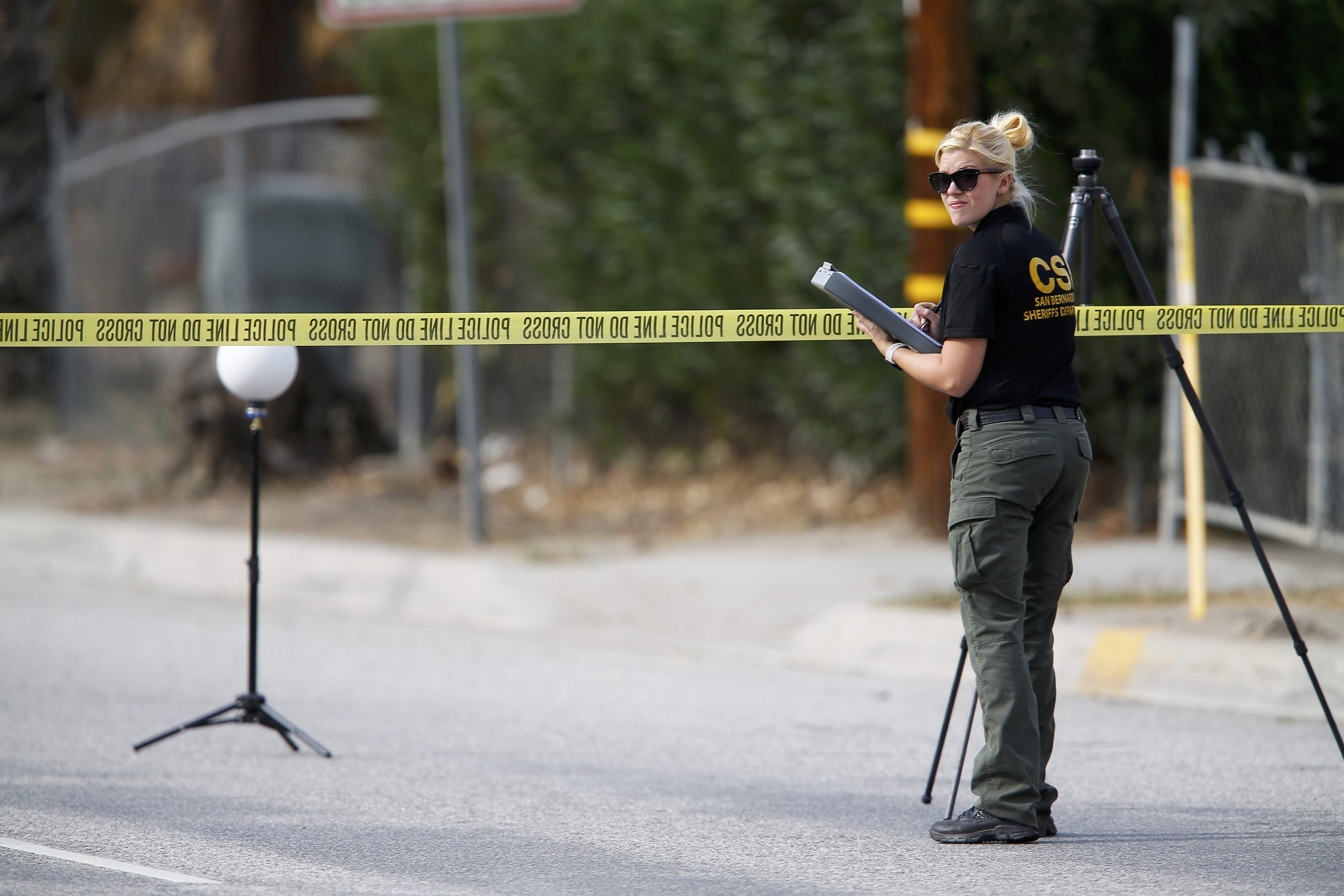 A Sheriff's Office Crime Scene Iinvestigator inspects the scene around an SUV where two suspects were shot by police following a mass shooting in San Bernardino, California December 3, 2015.