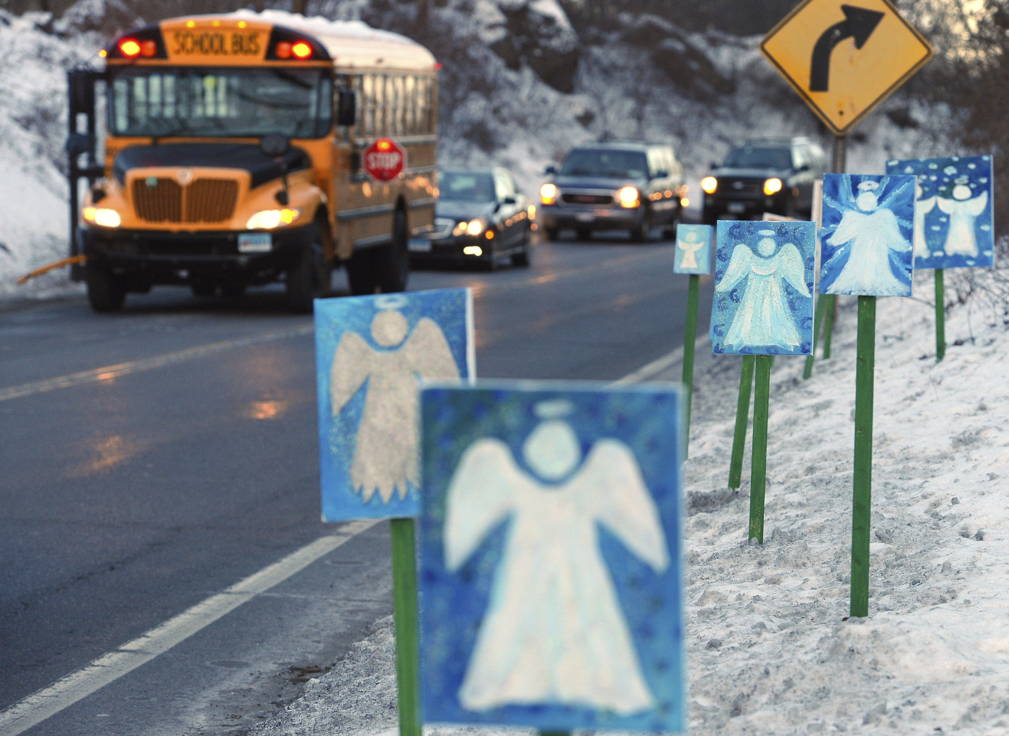 A bus traveling from Newtown, Conn., to Monroe stops near 26 angel signs posted along the roadside in Monroe, Conn., on Jan. 3, 2013, the first day of classes for Sandy Hook Elementary School students since the Dec. 14, 2012, shooting.