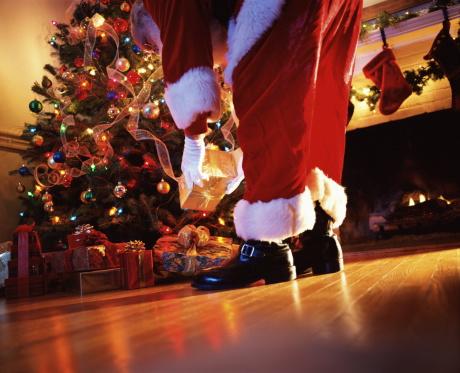 Santa Claus placing gift under tree