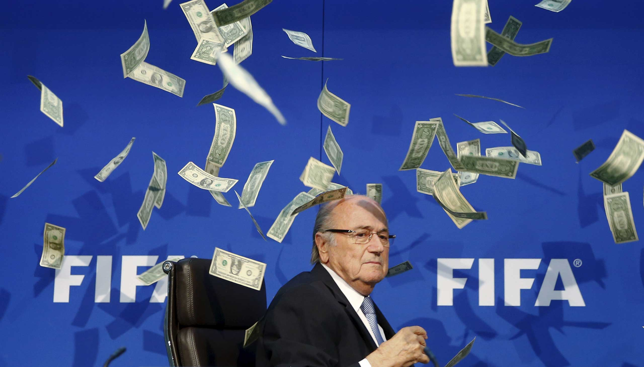 British comedian known as Lee Nelson (unseen) throws banknotes at FIFA President Sepp Blatter as he arrives for a news conference after the Extraordinary FIFA Executive Committee Meeting at the FIFA headquarters in Zurich, Switzerland, July 20, 2015.