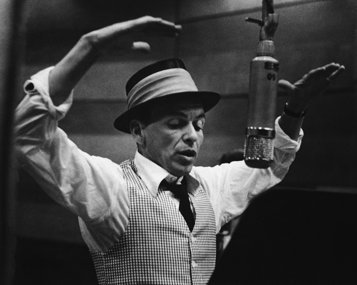 American singer and actor Frank Sinatra (1915 - 1998) gestures with his hands while singing into a microphone during a recording session in a studio at Capitol Records, early 1950s.