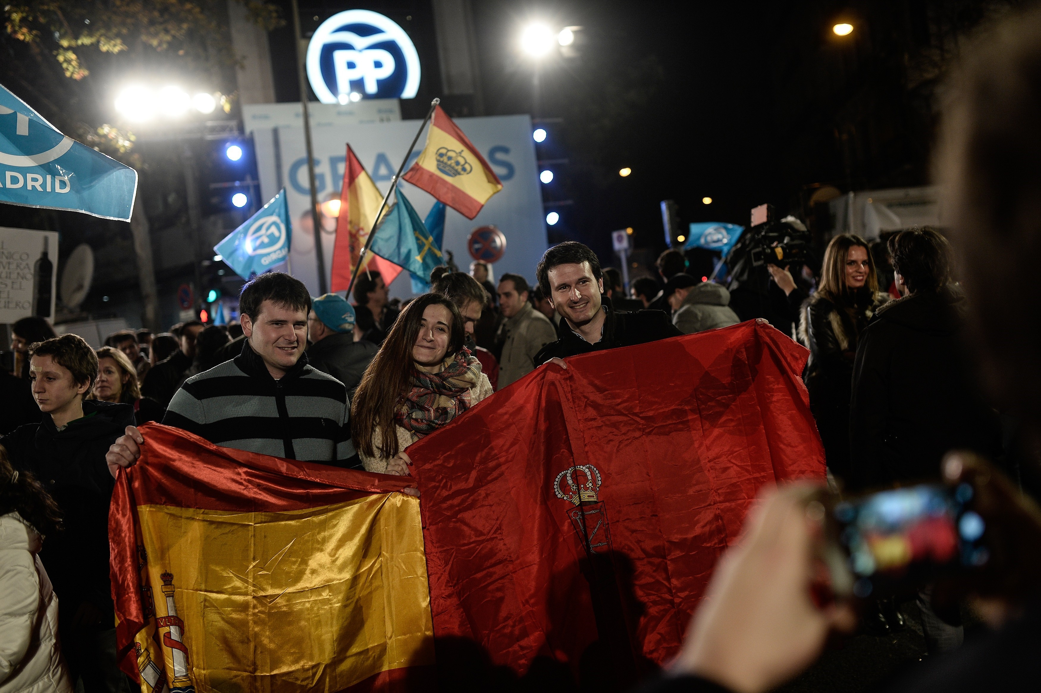 People gather as Spanish Prime Minister and Popular Party (PP) leader, Mariano Rajoy (not seen) gives a speech at his party headquarters'  balcony after Rajoy's party won the most votes of the General Elections during a public meeting with supporters in Madrid, Spain on Dec. 21, 2015.