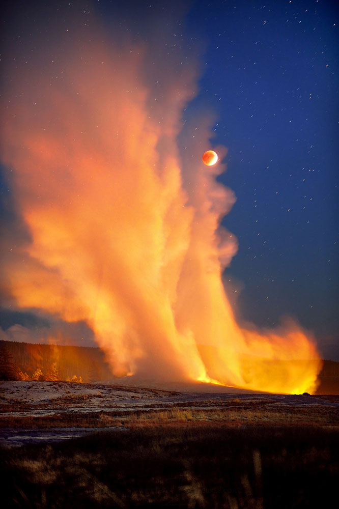 Old Faithful erupts during the super blood moon eclipse on Sept. 27, 2015 over Yellowstone National Park.