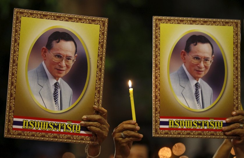 Well-wishers hold a lit candle and portraits of Thailand's King Bhumibol Adulyadej at Siriraj hospital, where a group has gathered to mark his 88th birthday, in Bangkok