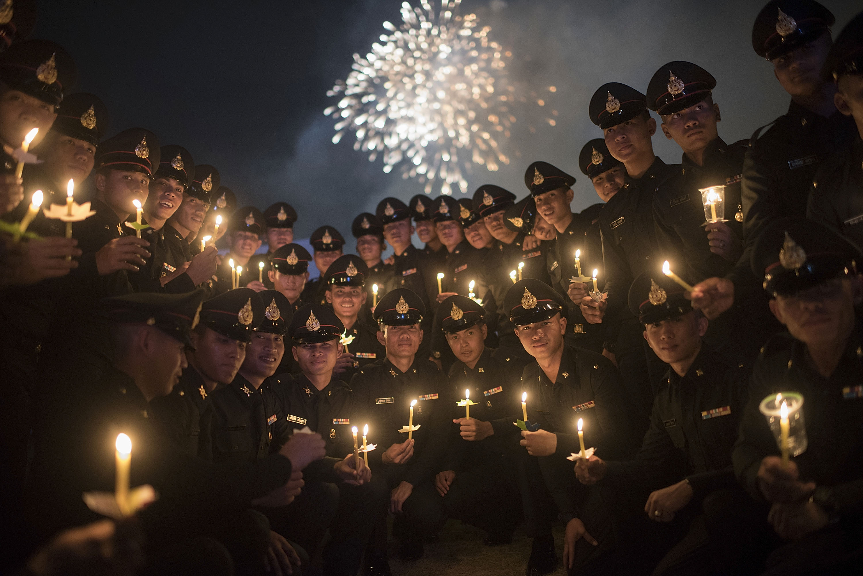 Thai policemen pose for a picture during a massive candle light ceremony for King Bhumibol Adulyadej's birthday at Sanam Luang in Bangkok, on Dec. 5, 2015.