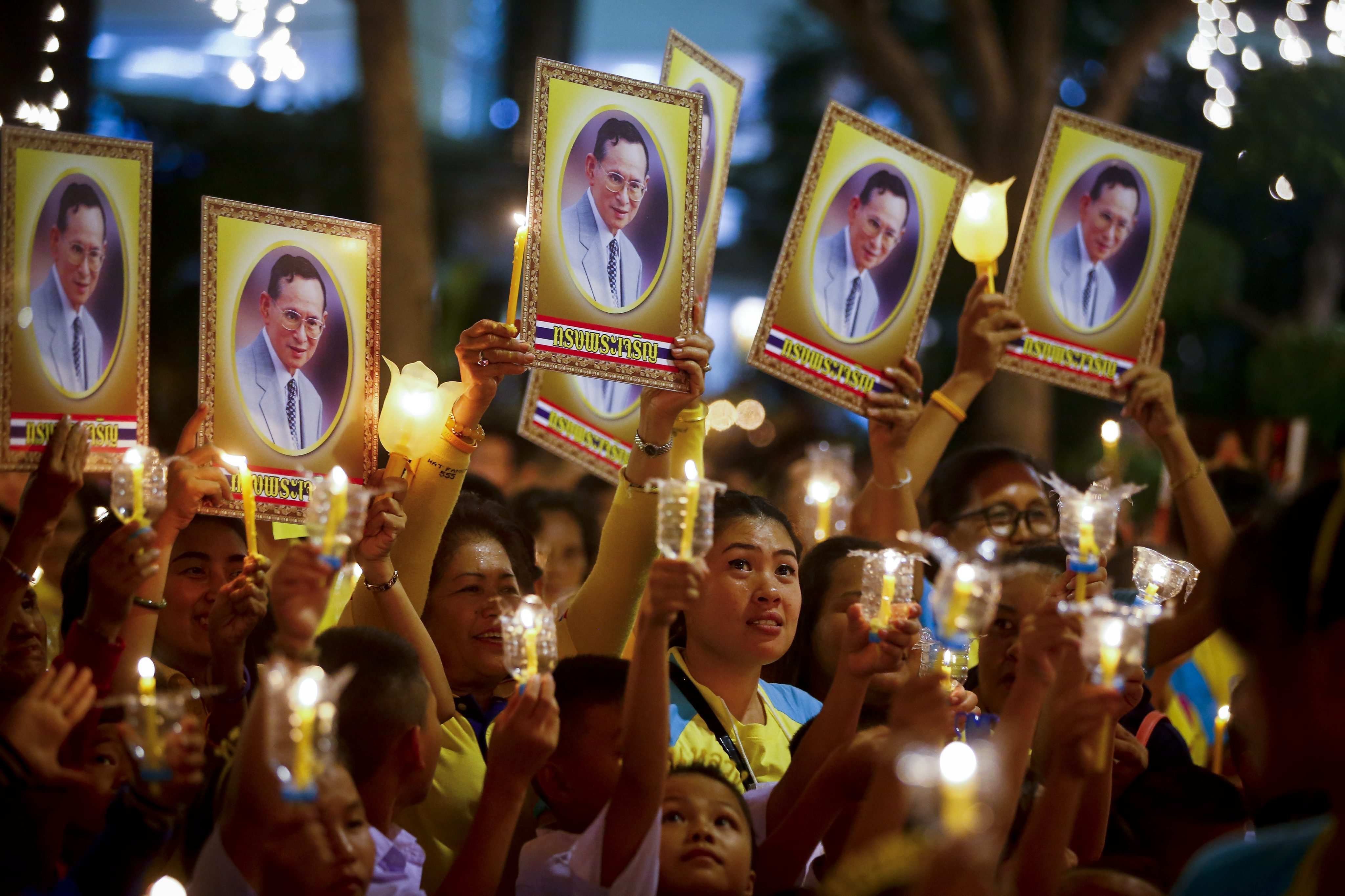 Thai well-wishers light candles and hold up portraits of Thai King Bhumibol Adulyadej during his 88th birthday celebration at Siriraj Hospital in Bangkok, on Dec. 5, 2015.