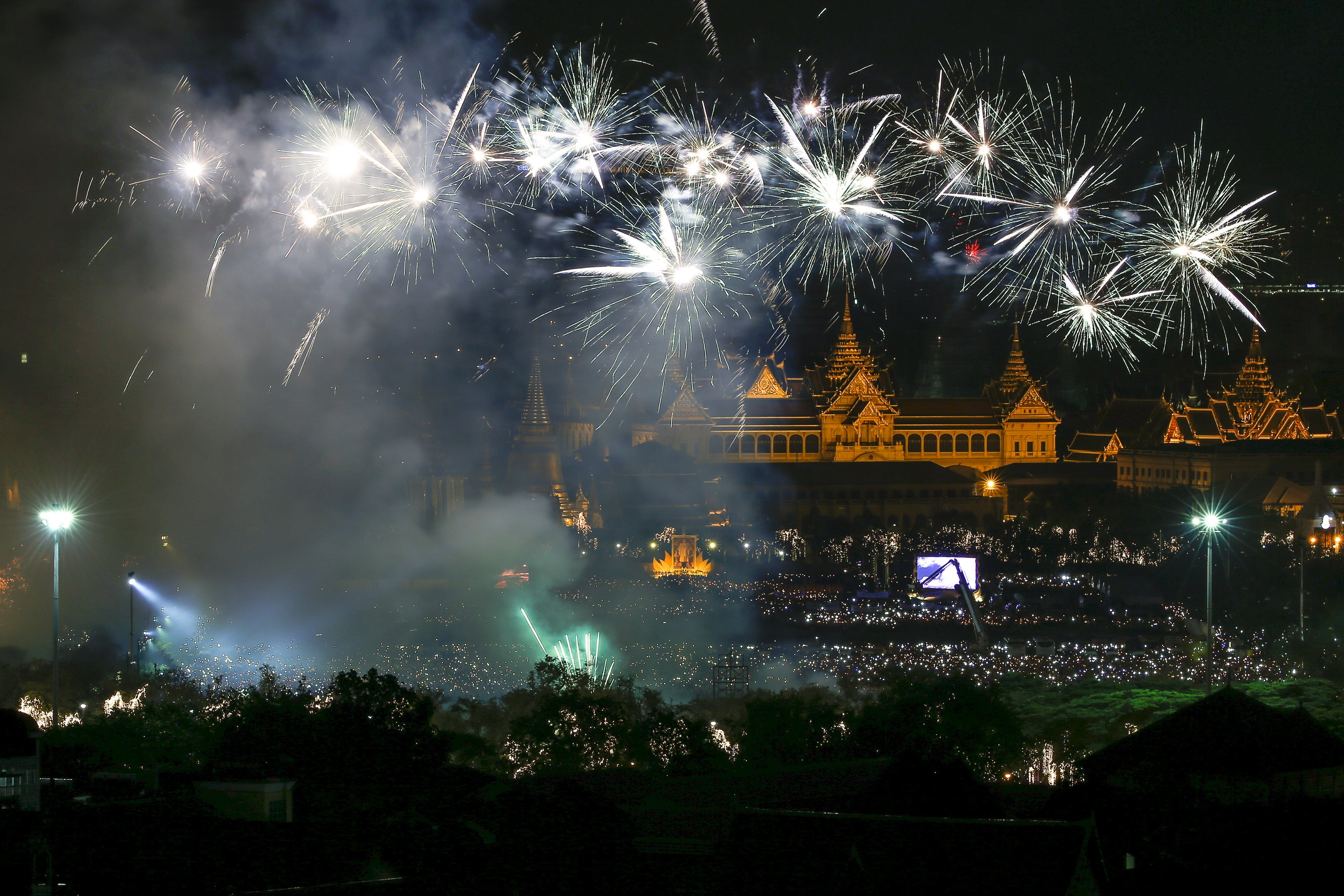 Fireworks over the Grand Palace as people hold candles to mark the birthday of Thailand's King Bhumibol Adulyadej to mark his 88th birthday in Bangkok, on Dec. 5, 2015.
