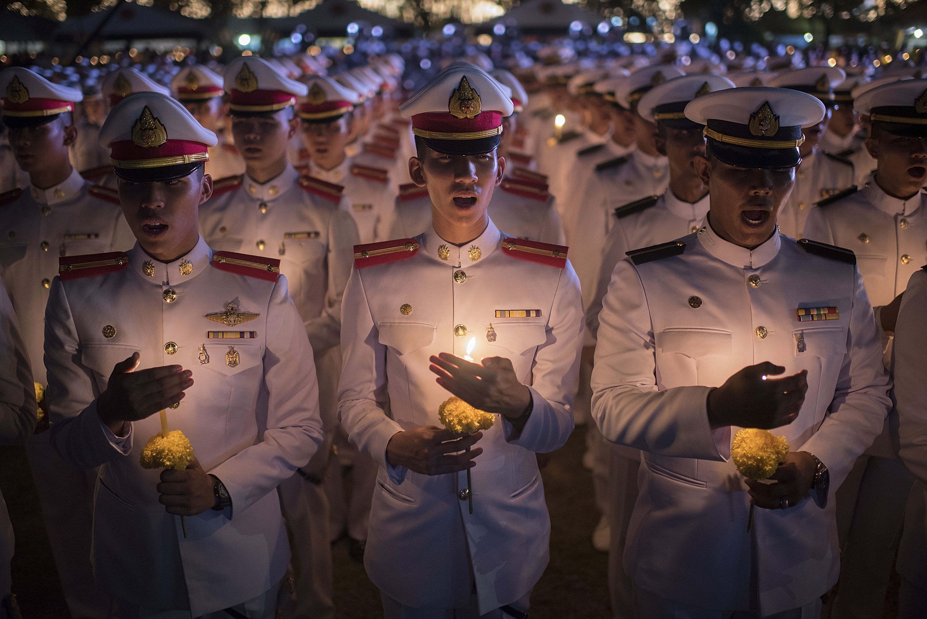 Thai soldiers hold candles during a massive candle light ceremony for King Bhumibol Adulyadej's birthday at Sanam Luang in Bangkok, on Dec. 5, 2015.
