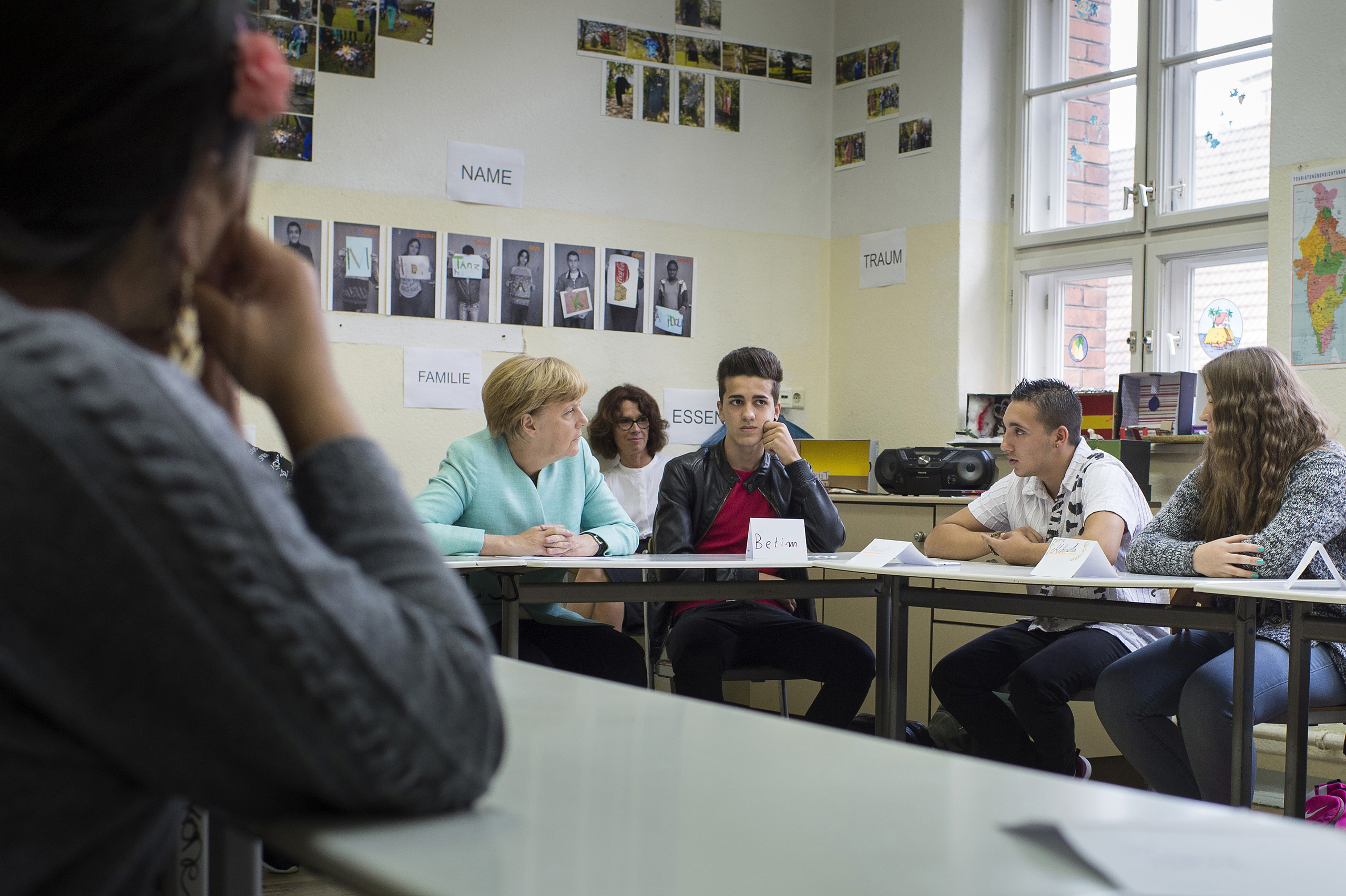 Federal Chancellor Angela Merkel talks with a student of a so called Willkommensklasse (welcome class) during her visit to Ferdinand-Freiligrath-school in Berlin-Kreuzberg. Three welcome classes with 36 places are established in this 230-student-school and should ease the school-start for the non-German-speaking refugees. Sept. 10, 2015.