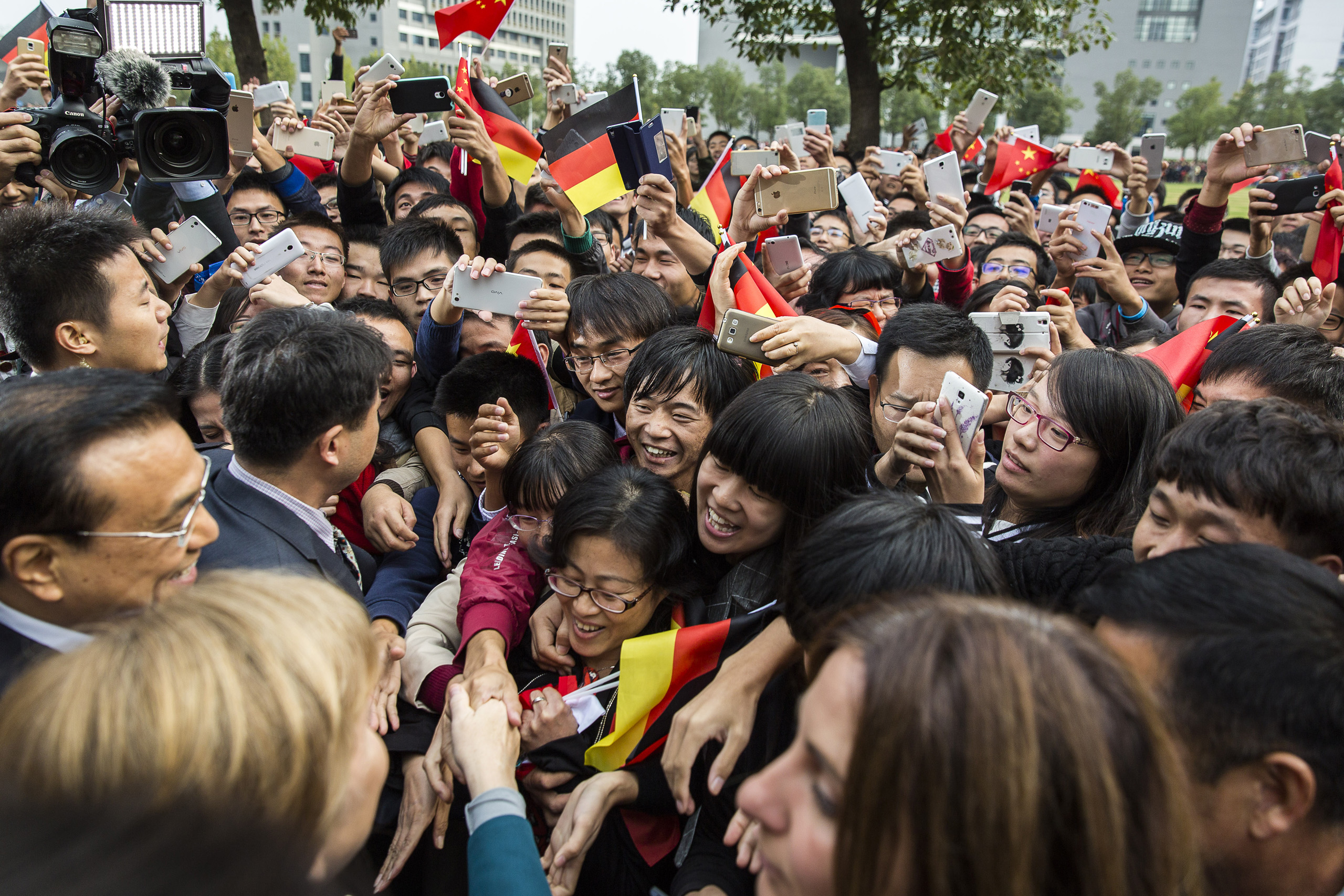 Chancellor Merkel and Chinese Premier Li Keqiang are being welcomed by students at Hefei University, China. Oct. 30, 2015.
