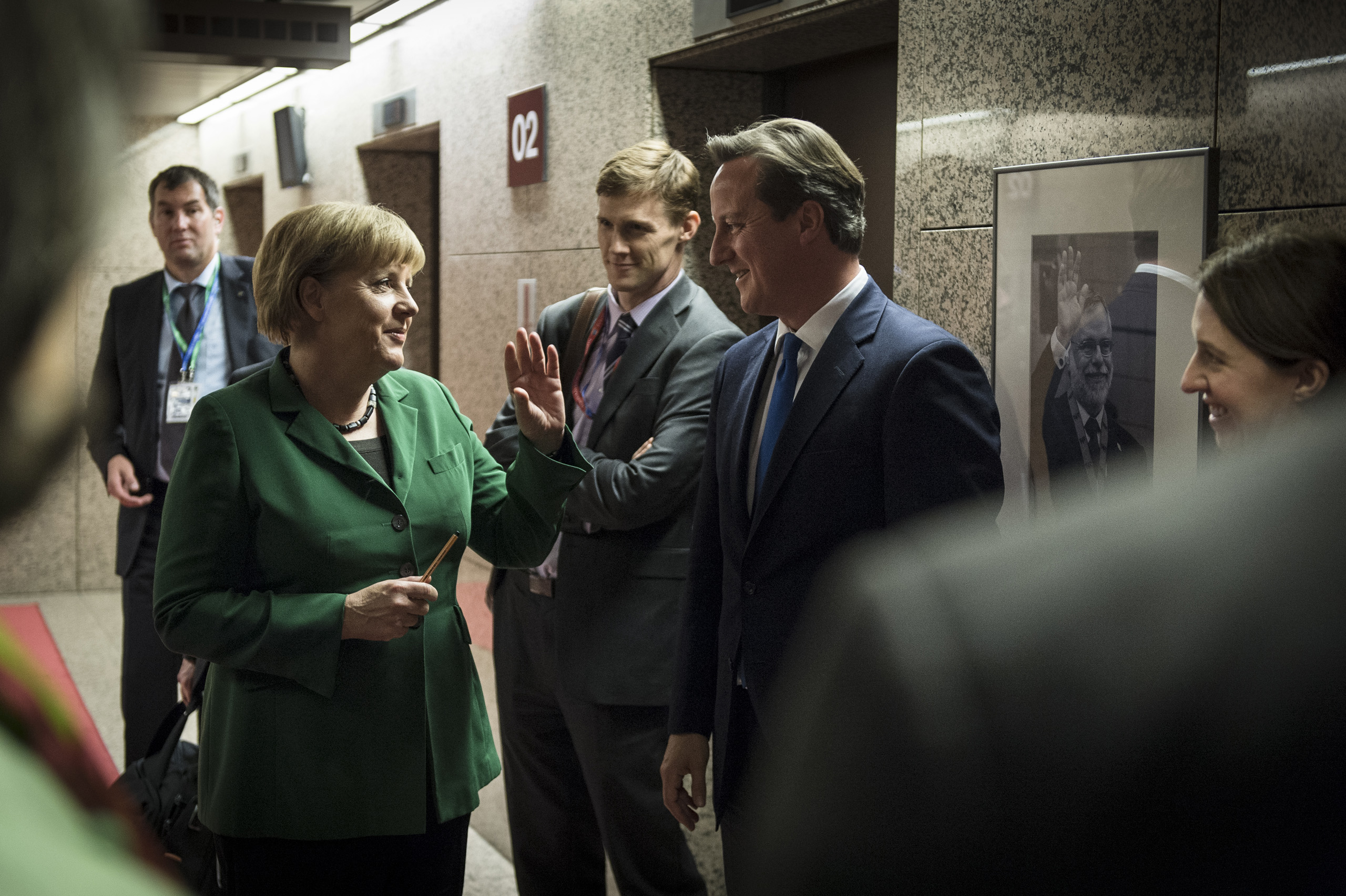 Chancellor Merkel and British Prime Minister David Cameron joke as they wait for their elevators after a European Council meeting in Brussels. Oct. 19, 2012.