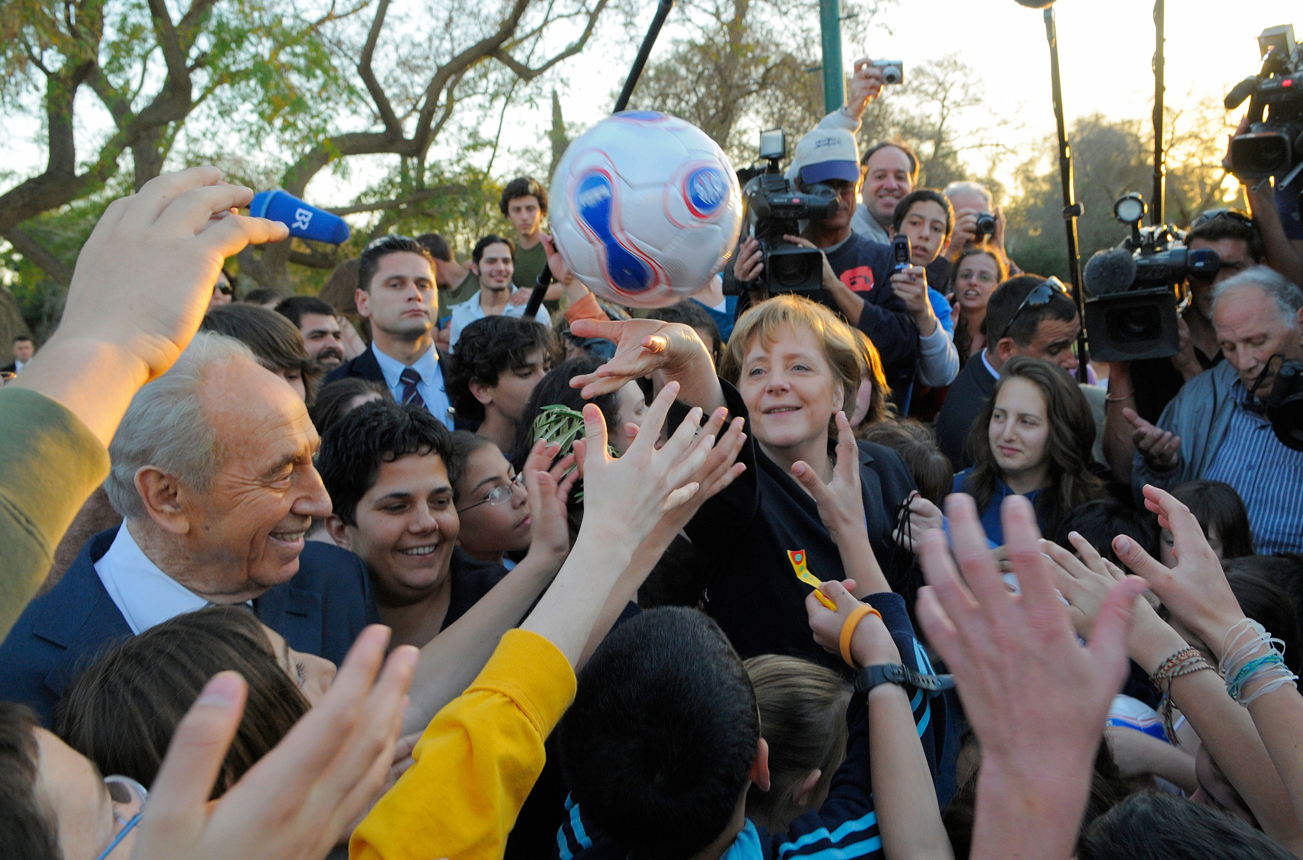 Chancellor Angela Merkel hands over soccer balls as a gift to kids, while she visits the Kibbuz Sde Boker togther with the then president of Israel, Shimon Peres. Merkel visited the Kibbuz, at the beginning of the first German-Israeli Government Consultations. March 16, 2008.