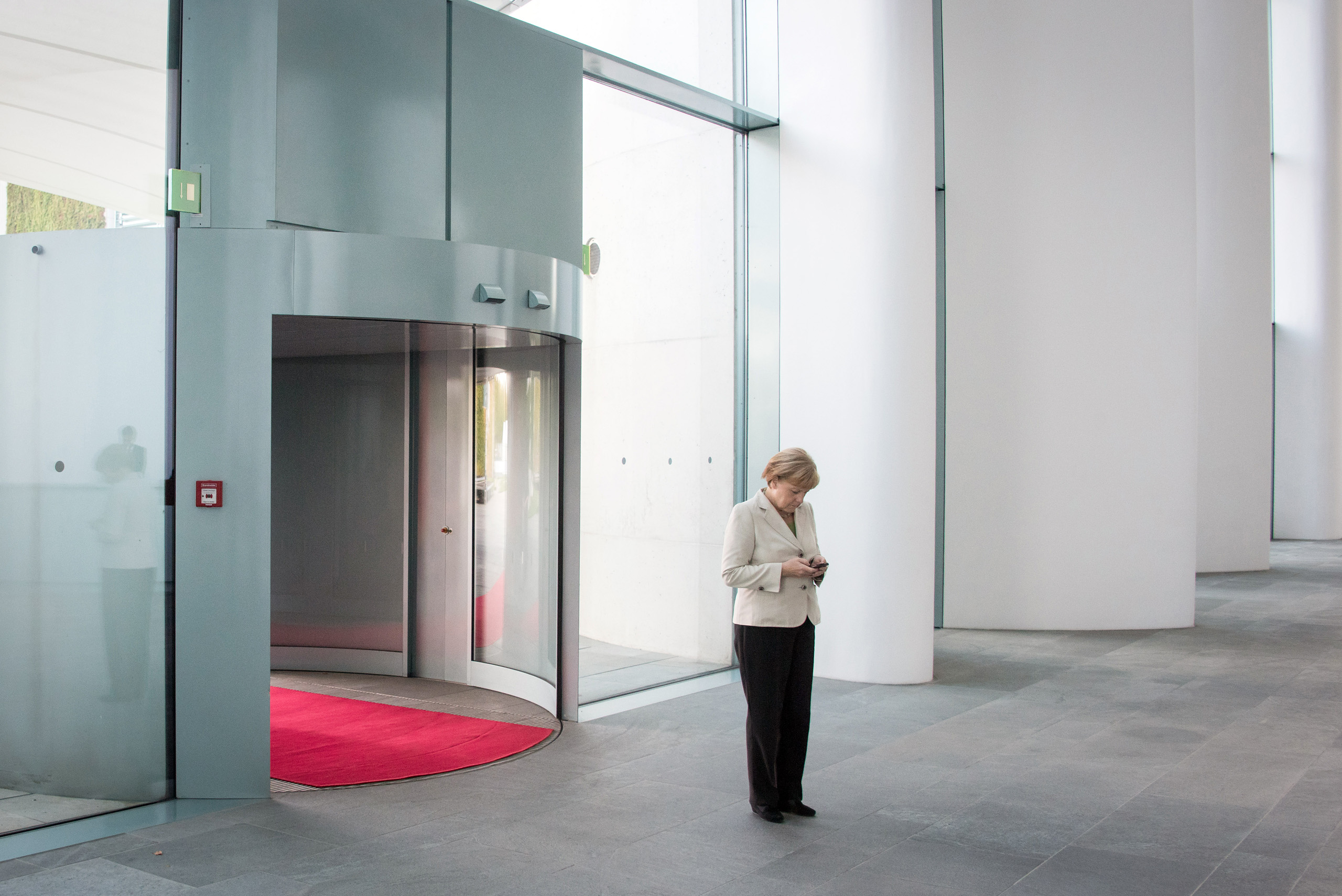 Federal Chancellor Angela Merkel checks her smartphone while waiting for the arrival of the heads of state for the Conference on Western Balkan in the Federal Chancellery in Berlin. Aug. 28, 2014.