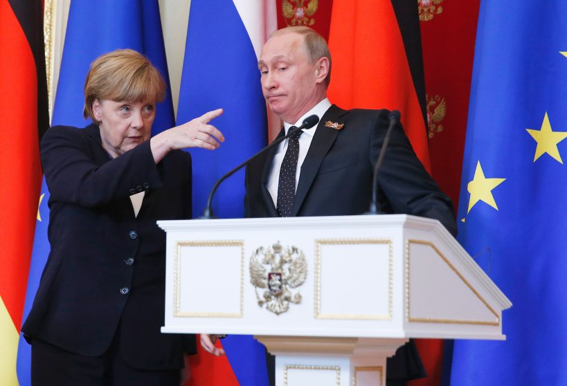 German Chancellor Angela Merkel gestures as Russian President Vladimir Putin looks on during a news conference after peace talks about east Ukraine at the Kremlin in Moscow on May 10, 2015.