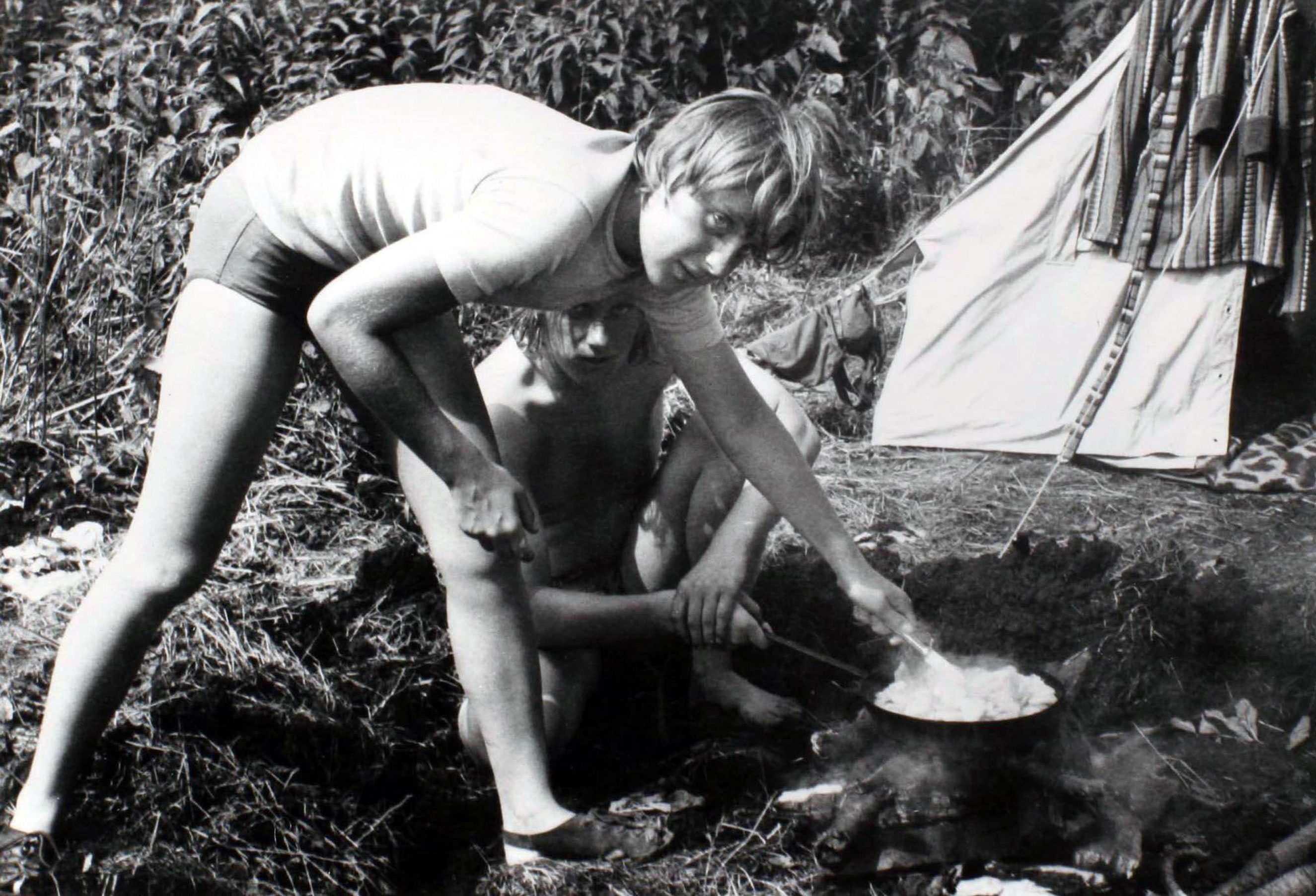 Angela Kasner prepares a meal on a campfire while camping with friends in Himmelpfort, German Democratic Republic in July 1973.