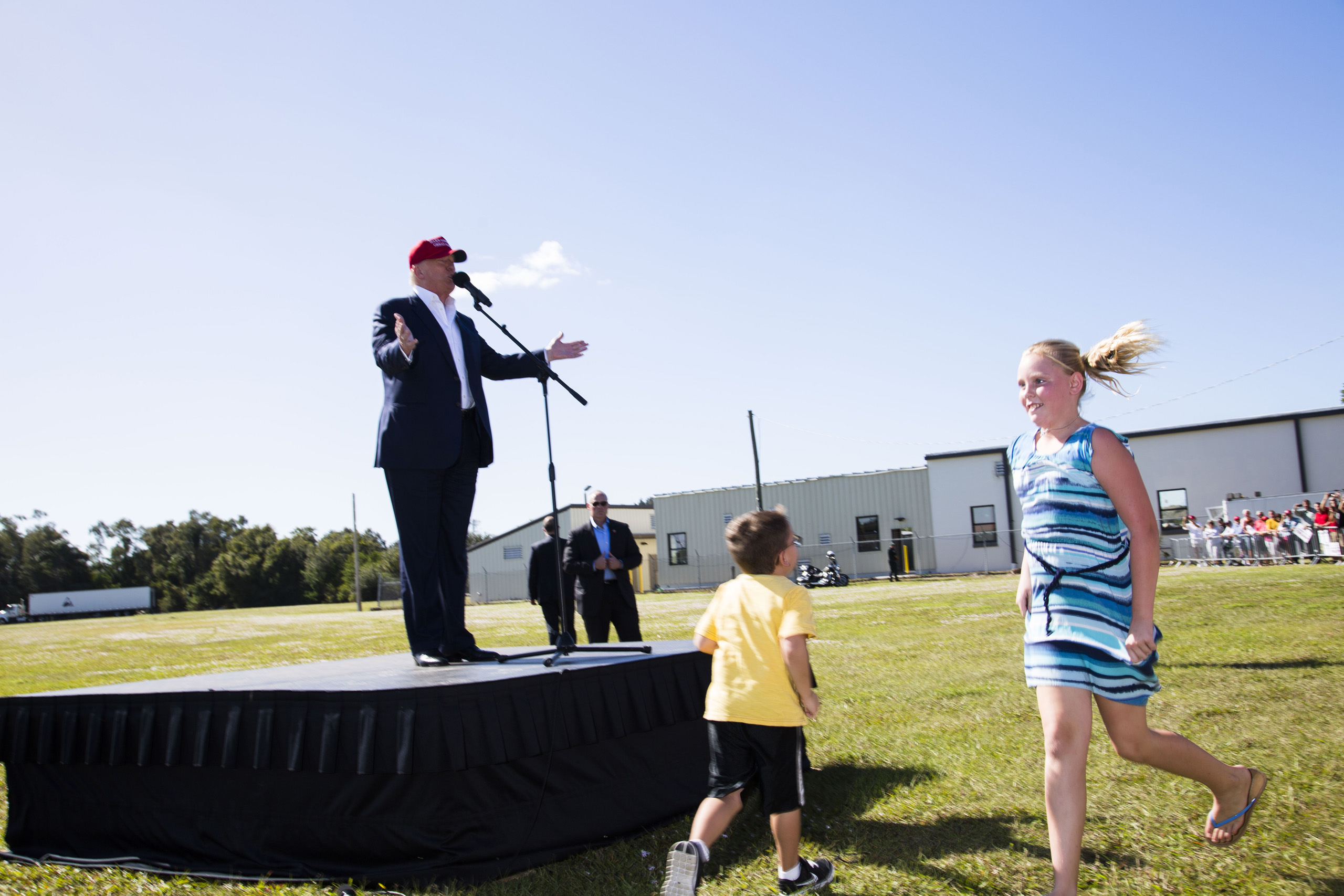 Republican presidential candidate Donald Trump speaks after arriving in his helicopter as a group of children race towards it for ride during a rally in Sarasota, Fla. Nov. 28, 2015.