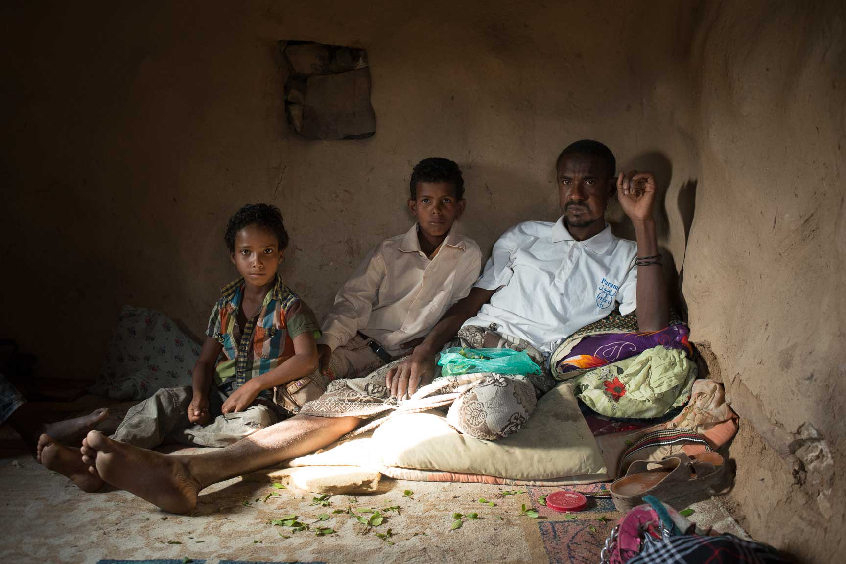 Fadhl Ahmad, a guard for the qat fields, sits with his two sons in his home on July 22, 2015. Since the war started, there has been no diesel to pump the water to water the qat, so he's had no work.