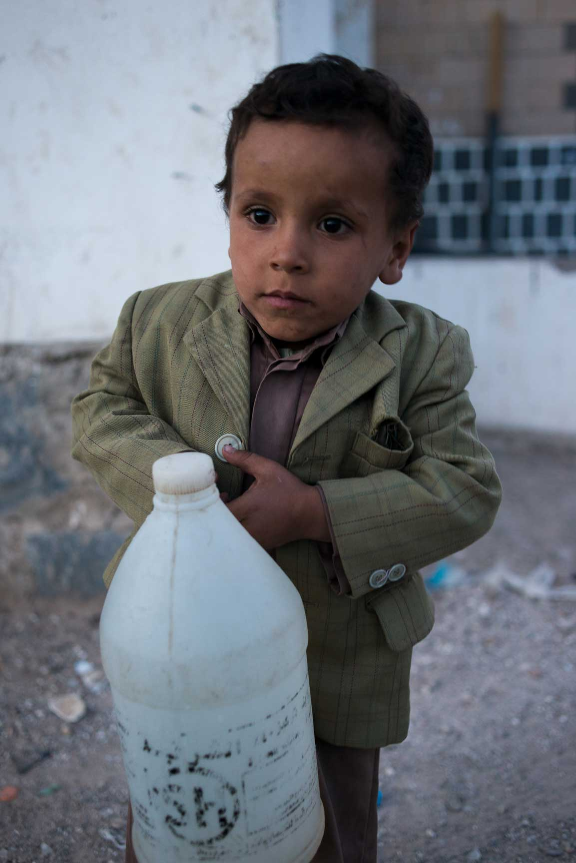 A Yemeni boy stands for a portrait after collecting water from a public tap near a mosque on Tuesday, June 2, 2015 in Sana'a, Yemen. Most homes did not have access to water before the war, and the dry conditions have only been exacerbated by the conflict, as most families cannot afford to purchase trucks that deliver water.