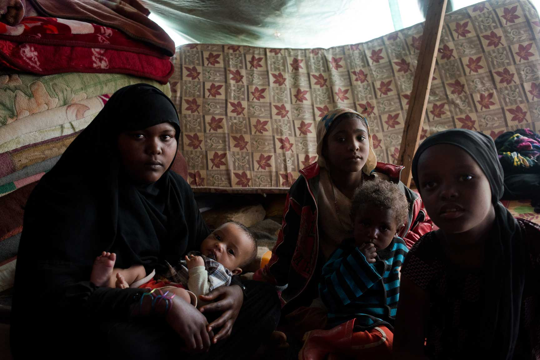 Children from a Yemeni family originally from the heavy-hit northern province of Sa'ada sit in their tent outside on July 7, 2015 in Amran, Yemen. They are members of Yemen's marginalized community, the Muhamashin, most of whom are not able to shelter in schools or family elsewhere.