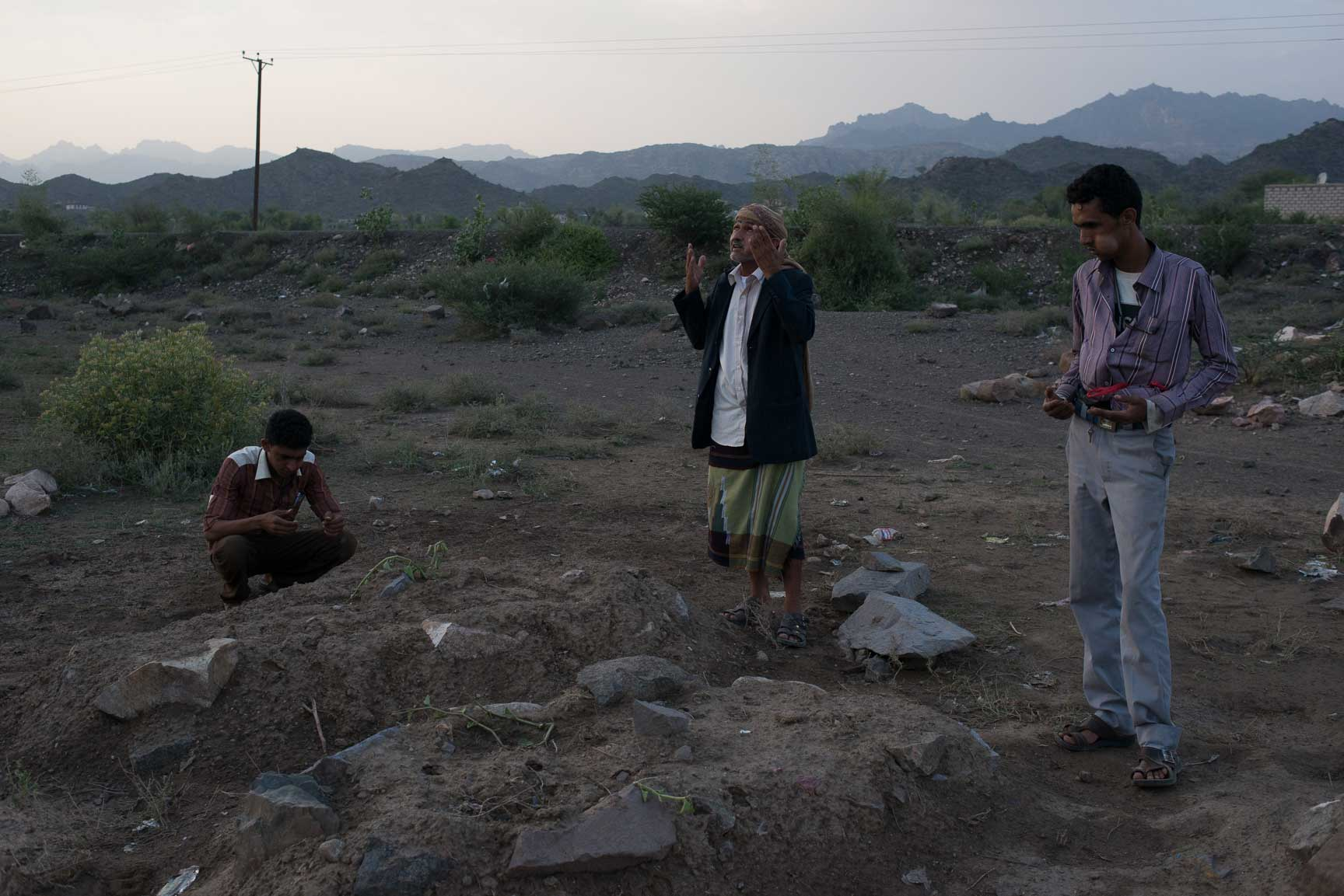 Muthana Abdullah Jaylani (center) prays over the graves of his relatives and neighbors who were killed by an airstrike, July 22, 2015. The strike killed at least five people, though only two were reported to the local MSF Hospital.