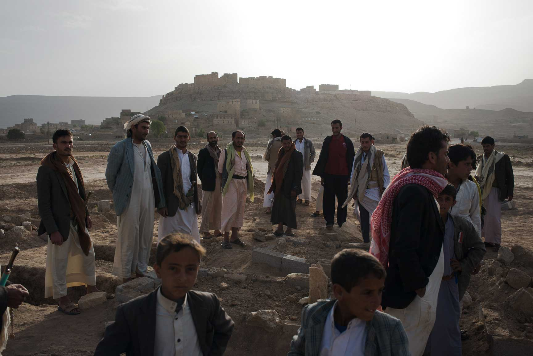 Yemeni men and boys visit the new cemetery in Al Joob, dug specifically to accommodate the 30 men, women and children who were killed between two strikes on a public market and along a roadside on July 7, 2015. Some had already been buried, but other graves lay empty, waiting for the bodies to come from the morgue in Amran or Sanaa. More hopeful cases were sent to the better equipped hospitals in Sanaa, but most died on the way there.